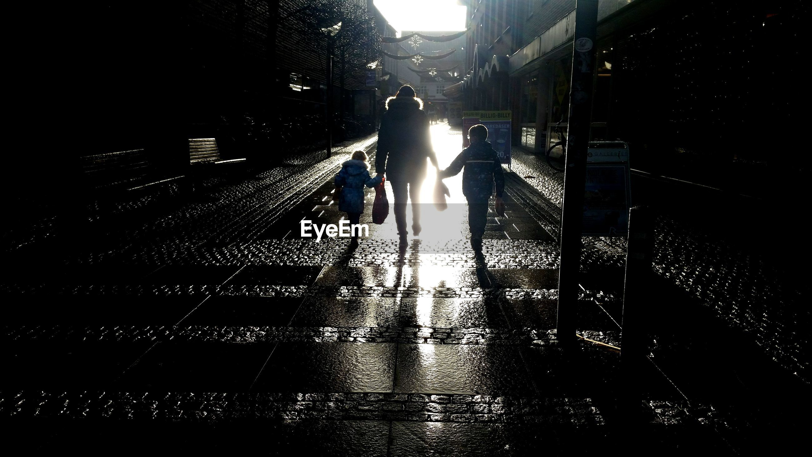 Rear view of mother walking with children against buildings on sunny day