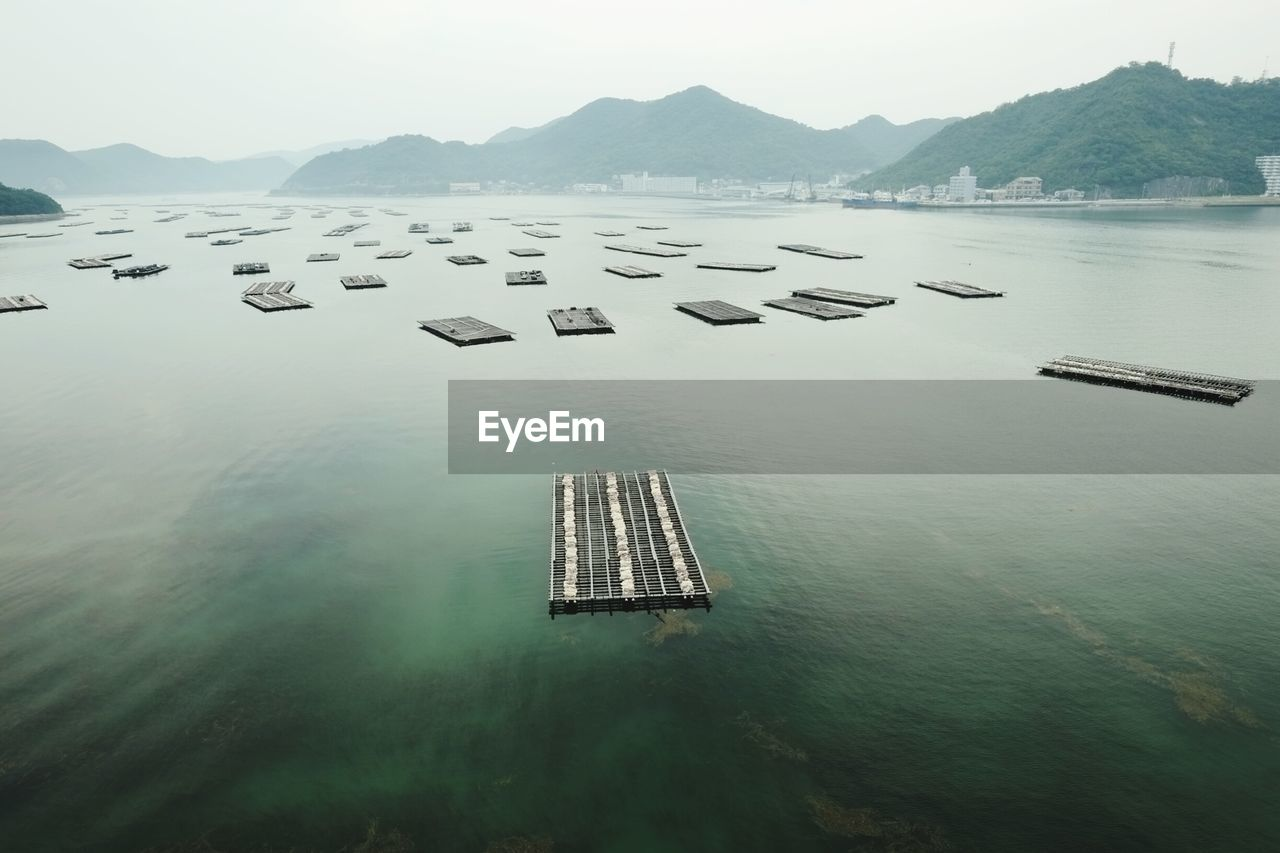 High Angle View Of Rafts On Sea Against Mountains