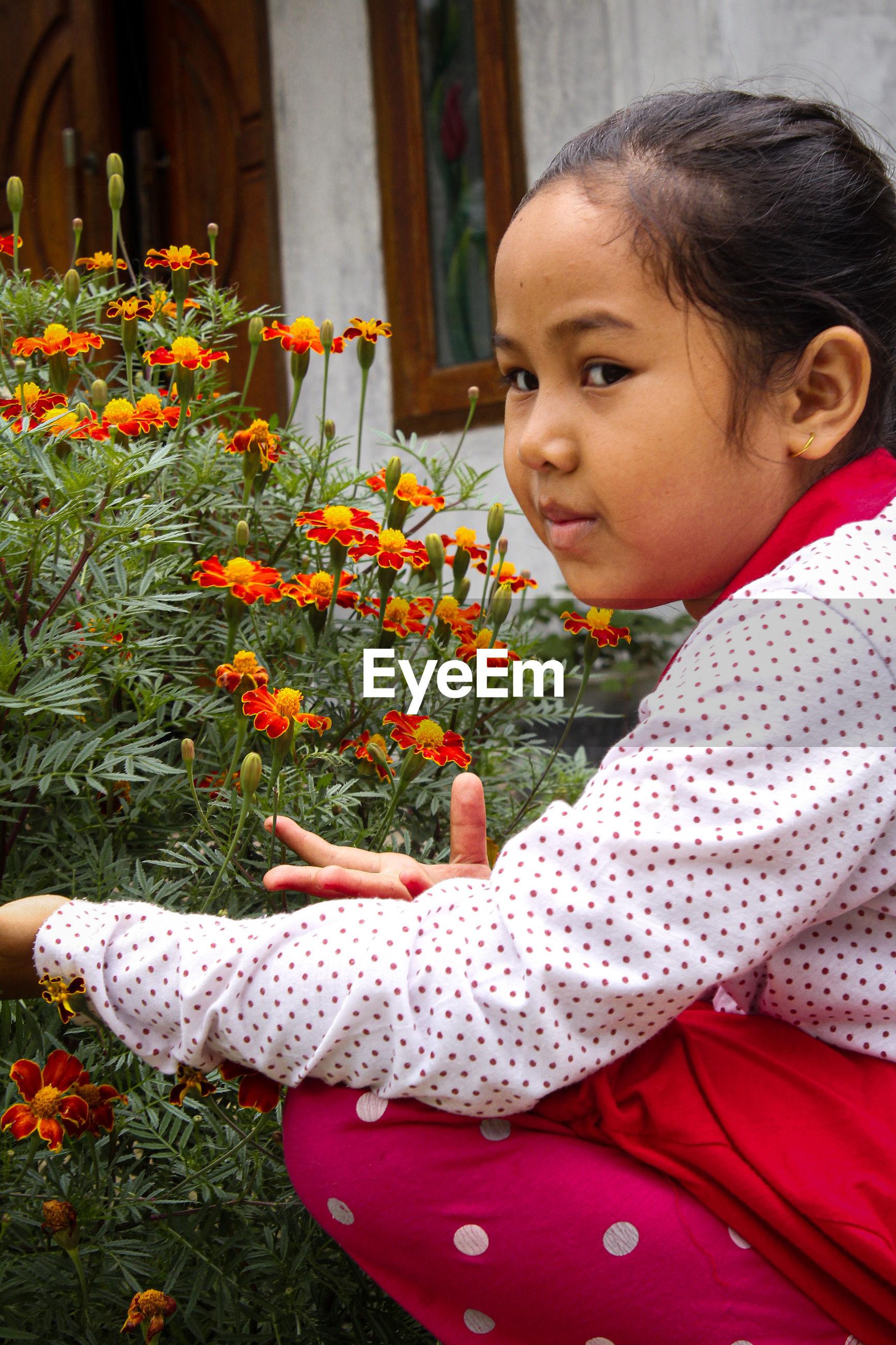 Side view of cute girl looking at red flowering plants