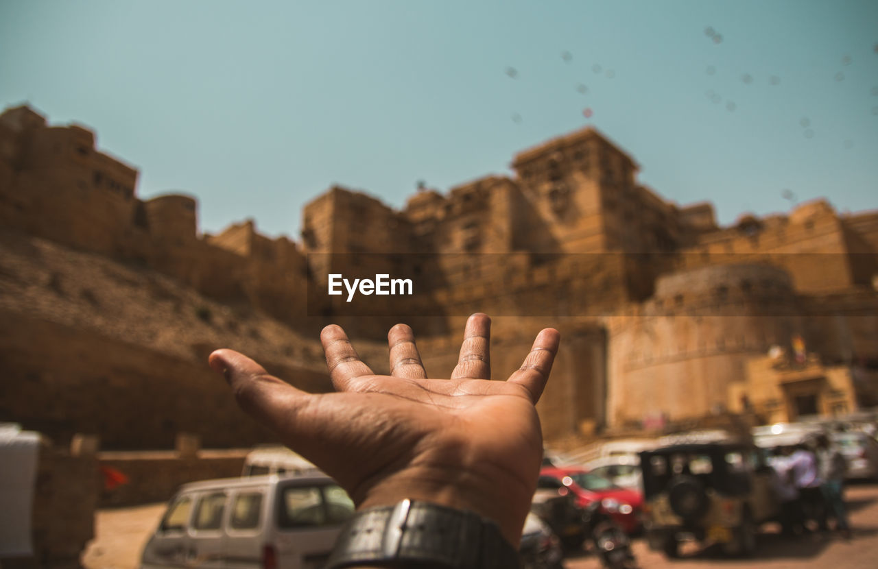 human hand, hand, real people, built structure, human body part, building exterior, sky, one person, architecture, finger, lifestyles, human finger, gesturing, mode of transportation, body part, unrecognizable person, men, day, transportation, outdoors