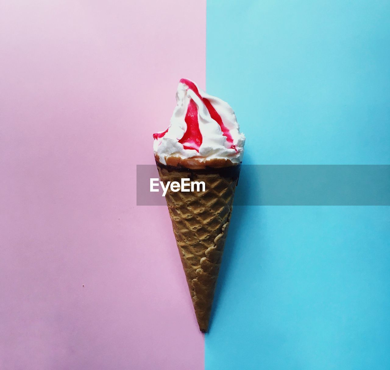 Close-up of ice cream cone on colored background