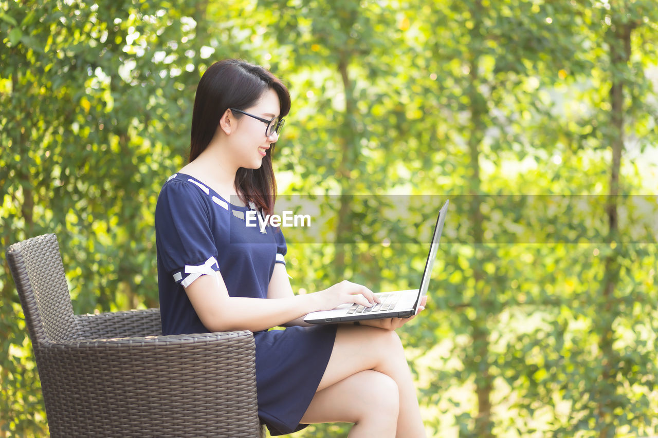 sitting, young adult, real people, glasses, one person, eyeglasses, young women, wireless technology, three quarter length, technology, lifestyles, adult, casual clothing, connection, leisure activity, seat, communication, day, using laptop, beautiful woman, hairstyle