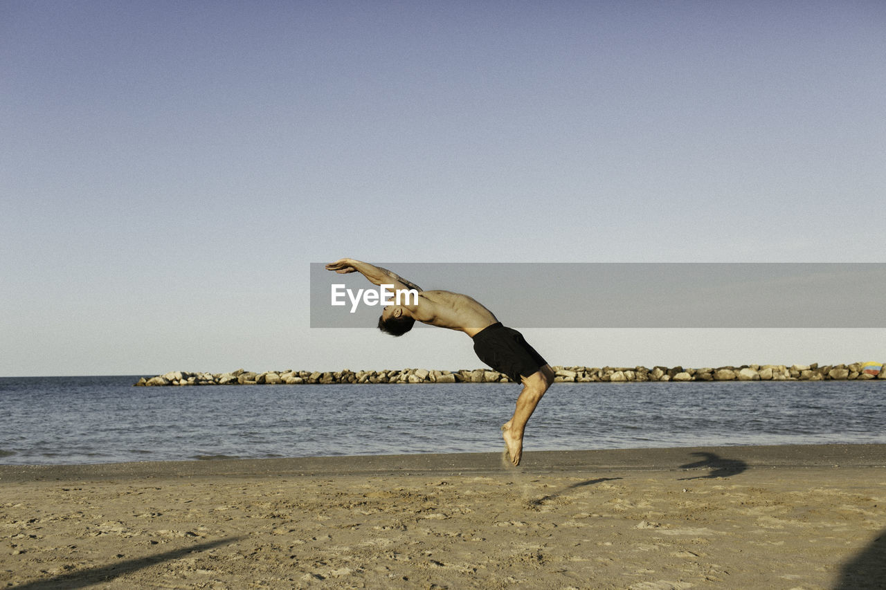 Full Length Of Shirtless Man Jumping At Beach Against Clear Sky