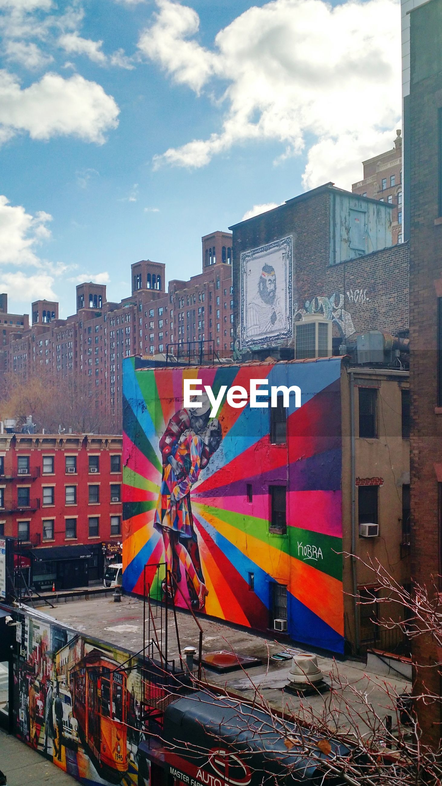 building exterior, architecture, built structure, sky, city, graffiti, cloud - sky, street, multi colored, residential structure, transportation, residential building, outdoors, day, building, cloud, text, road, city life, no people