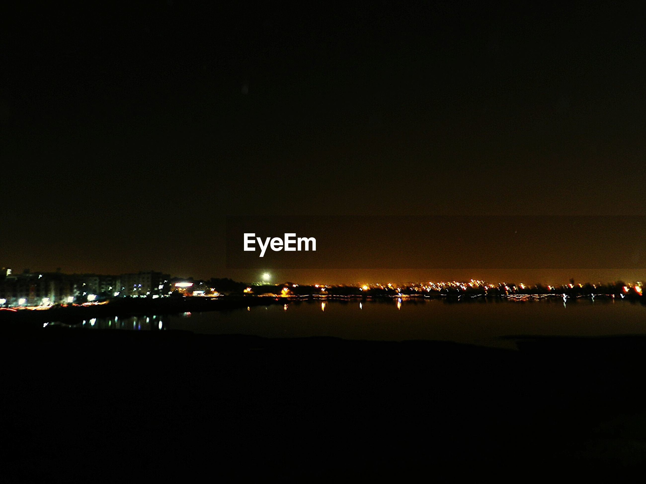 Scenic view of river by illuminated city against clear sky at night