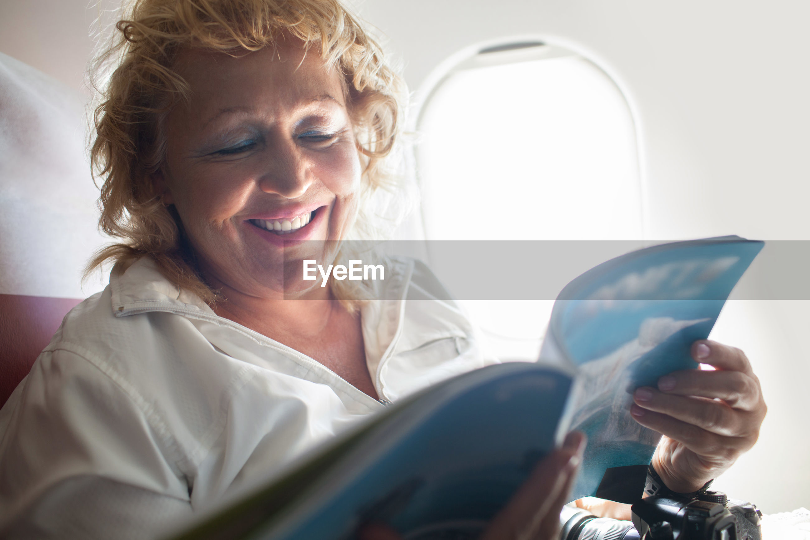 Smiling woman reading magazine while sitting in airplane