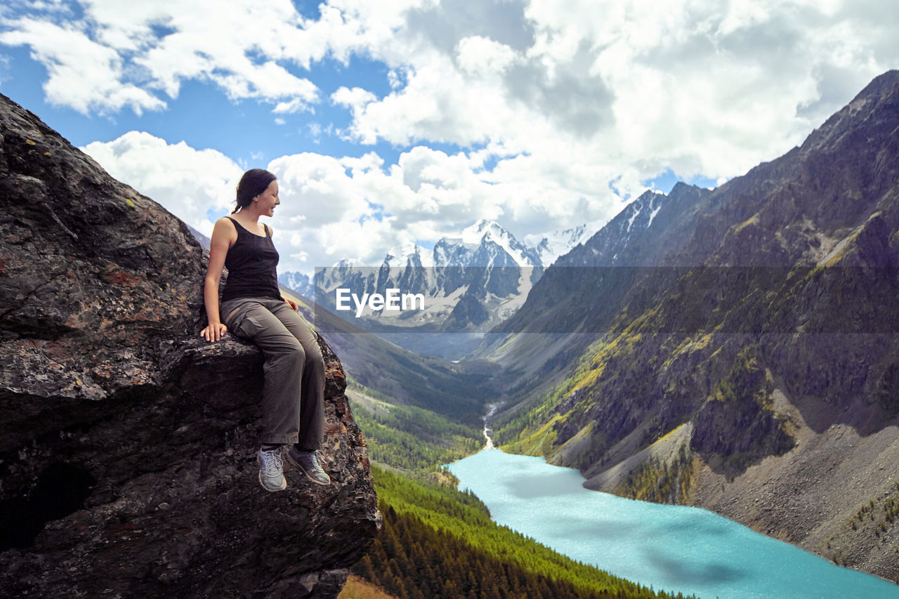 Full length of woman sitting sitting on cliff against mountain