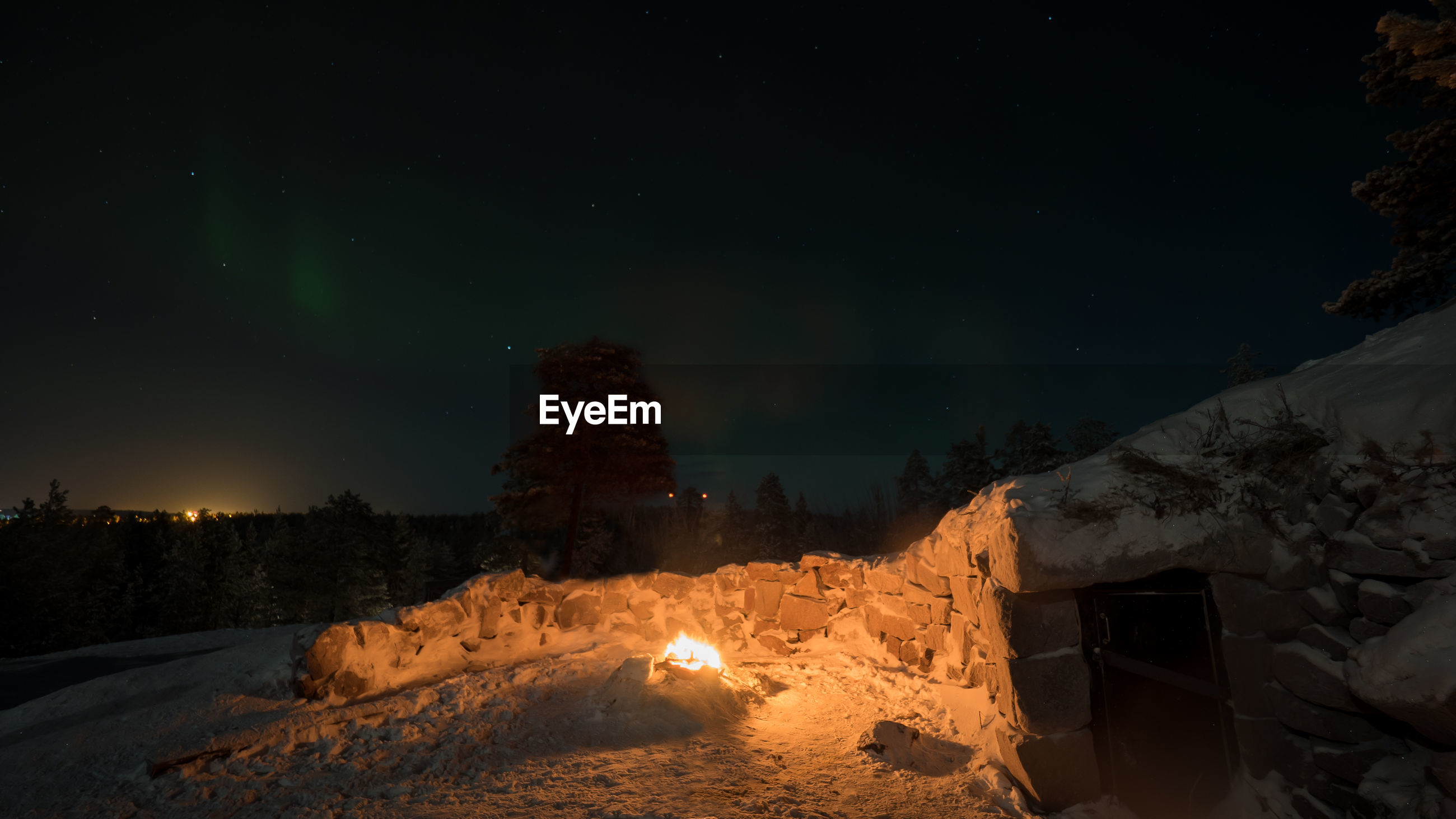 VIEW OF BONFIRE ON SNOW COVERED LAND AT NIGHT