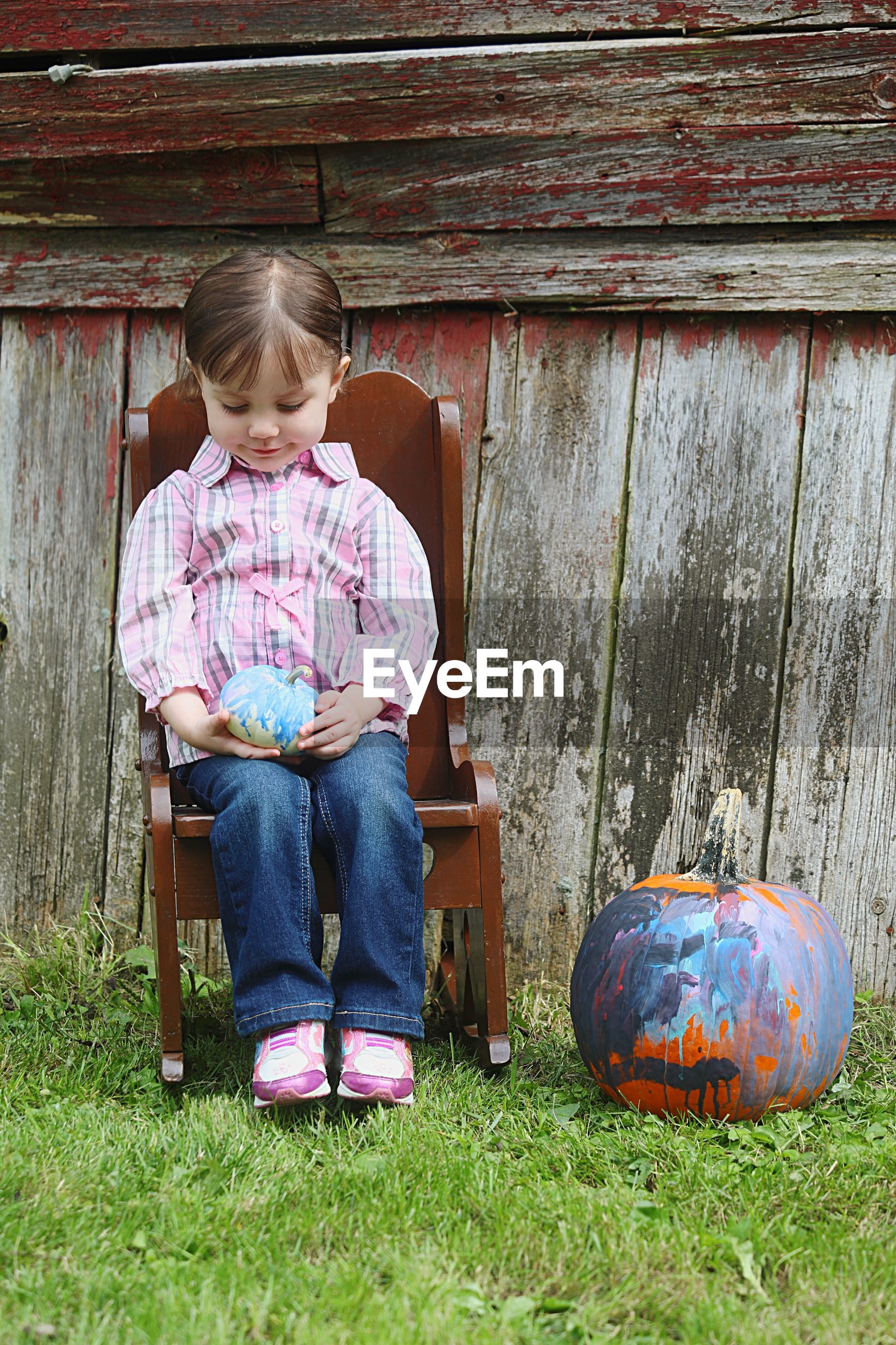 Full length of girl sitting on chair by pumpkin during halloween