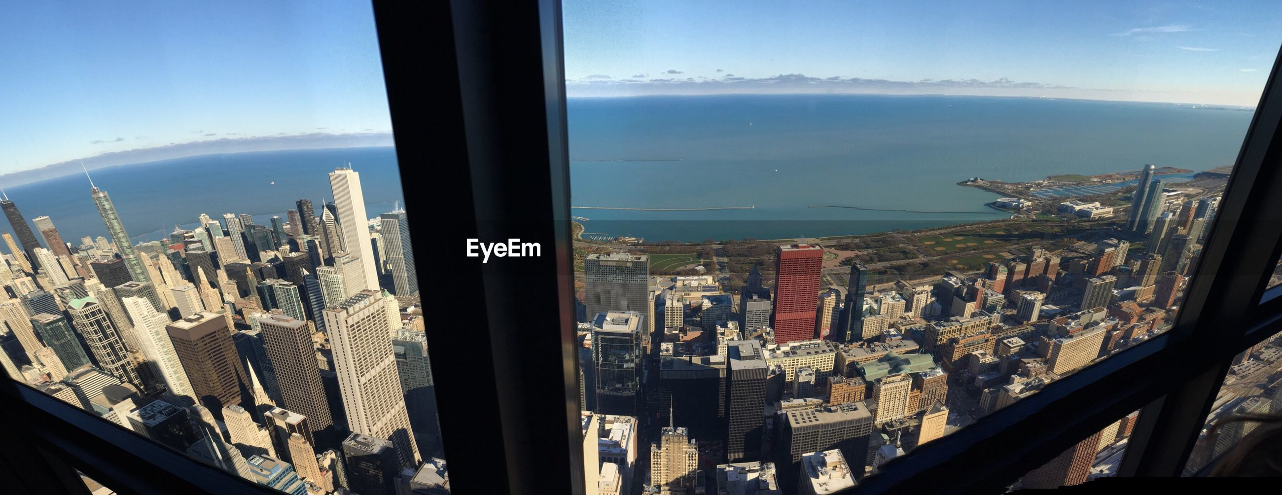 Sea and buildings seen through glass window