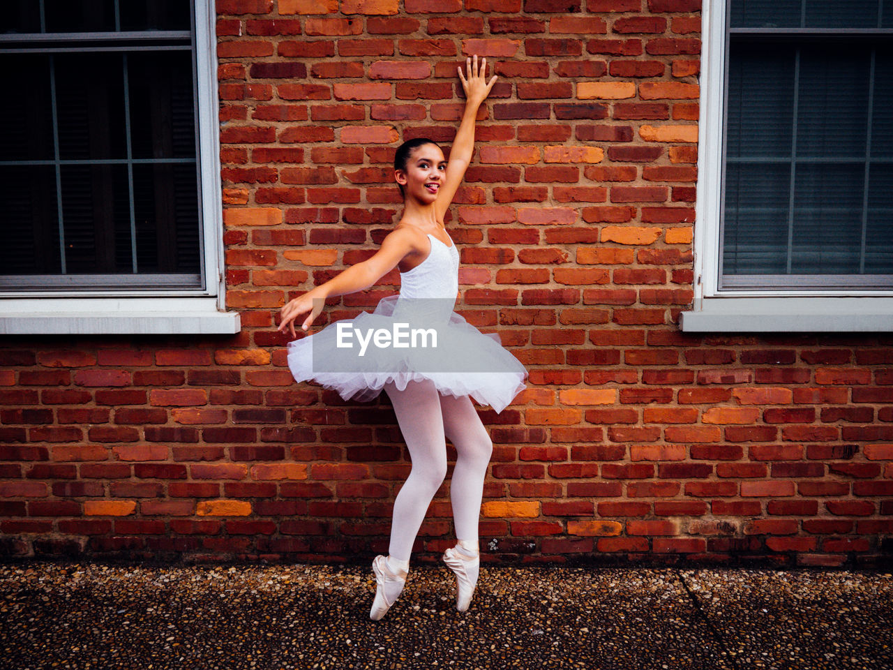 full length, one person, young adult, brick, ballet, ballet dancer, brick wall, human arm, architecture, arms raised, limb, dancing, tutu, young women, human limb, looking at camera, women, portrait, body part, beautiful woman, fashion, skill, outdoors