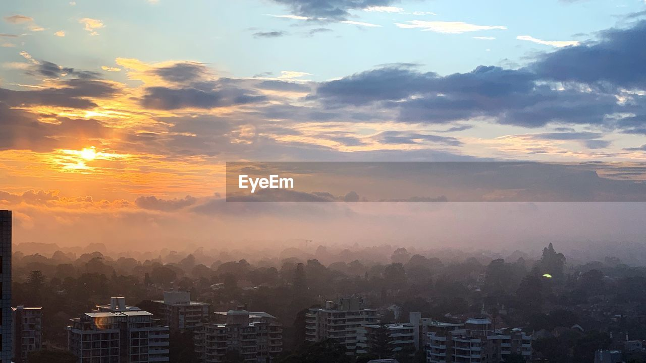 sky, cloud - sky, building exterior, sunset, architecture, city, built structure, building, nature, no people, cityscape, beauty in nature, fog, orange color, sun, sunlight, outdoors, landscape, scenics - nature, residential district, skyscraper, office building exterior