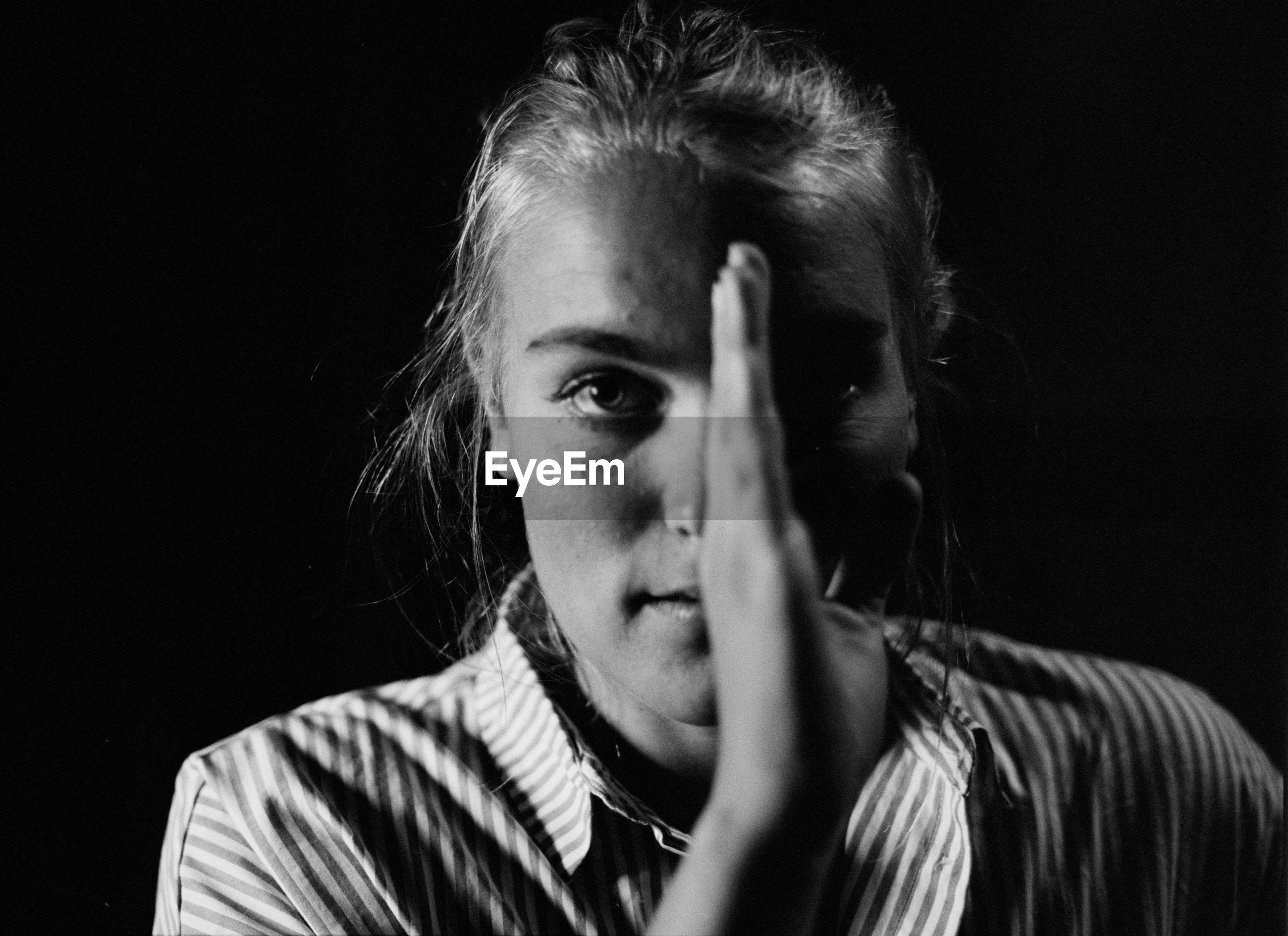 Close-up portrait woman against black background