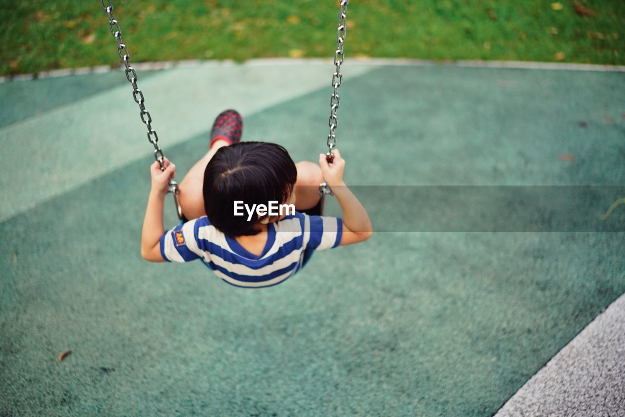 Rear View Of Boy Sitting On Swing At Playground