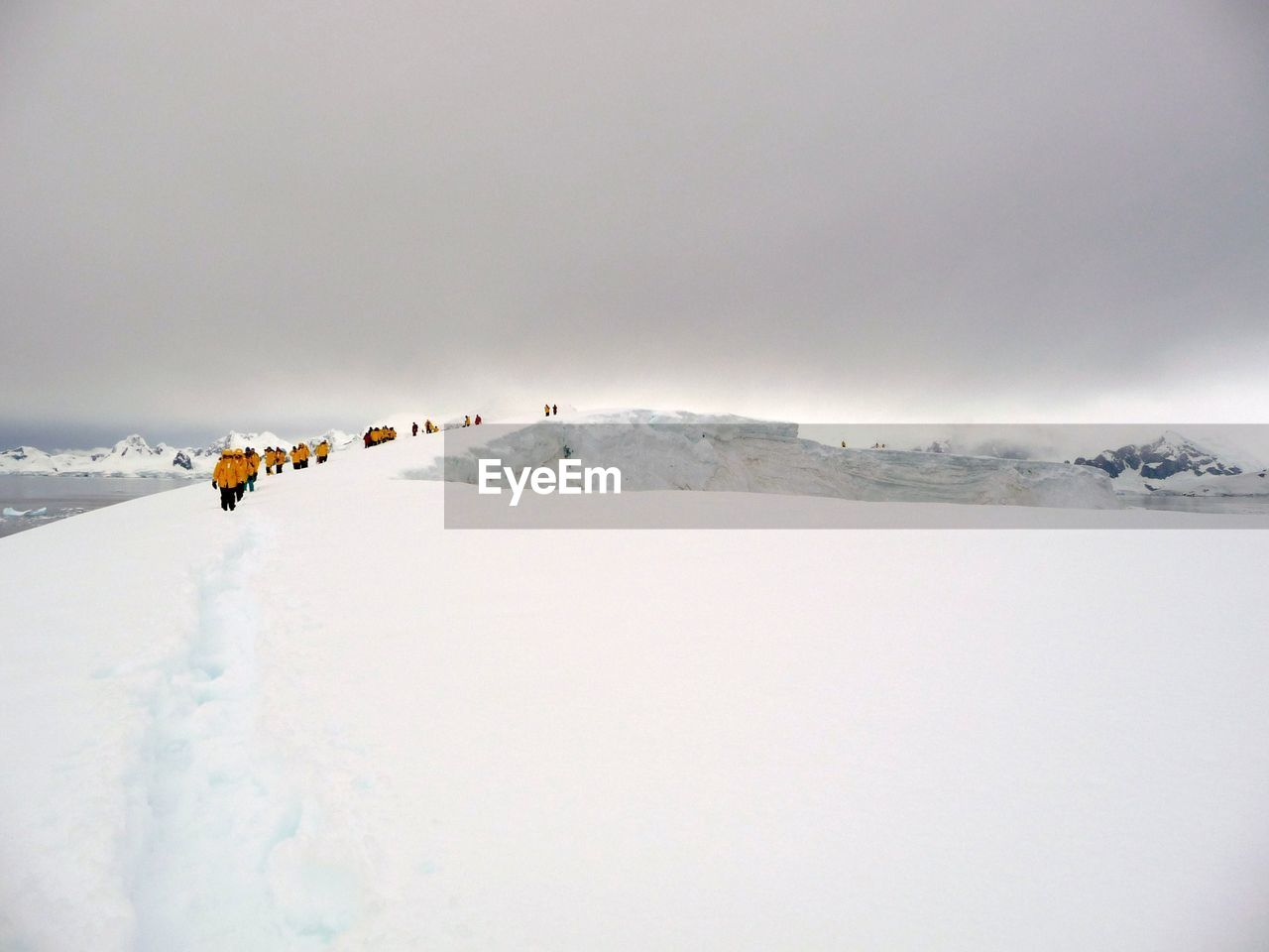 People Walking On Snow Covered Landscape Against Sky At Antarctica