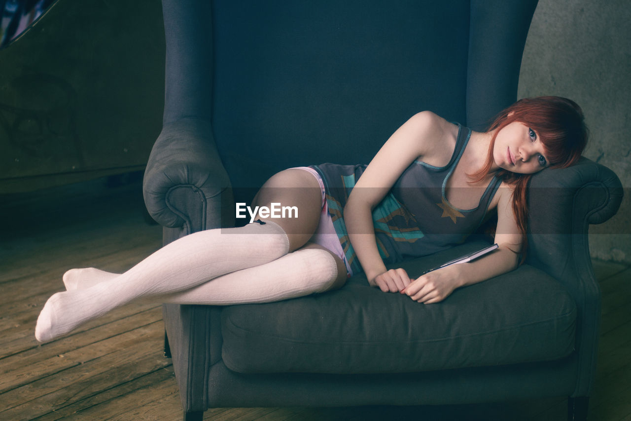 Portrait Of Young Woman Lying On Armchair