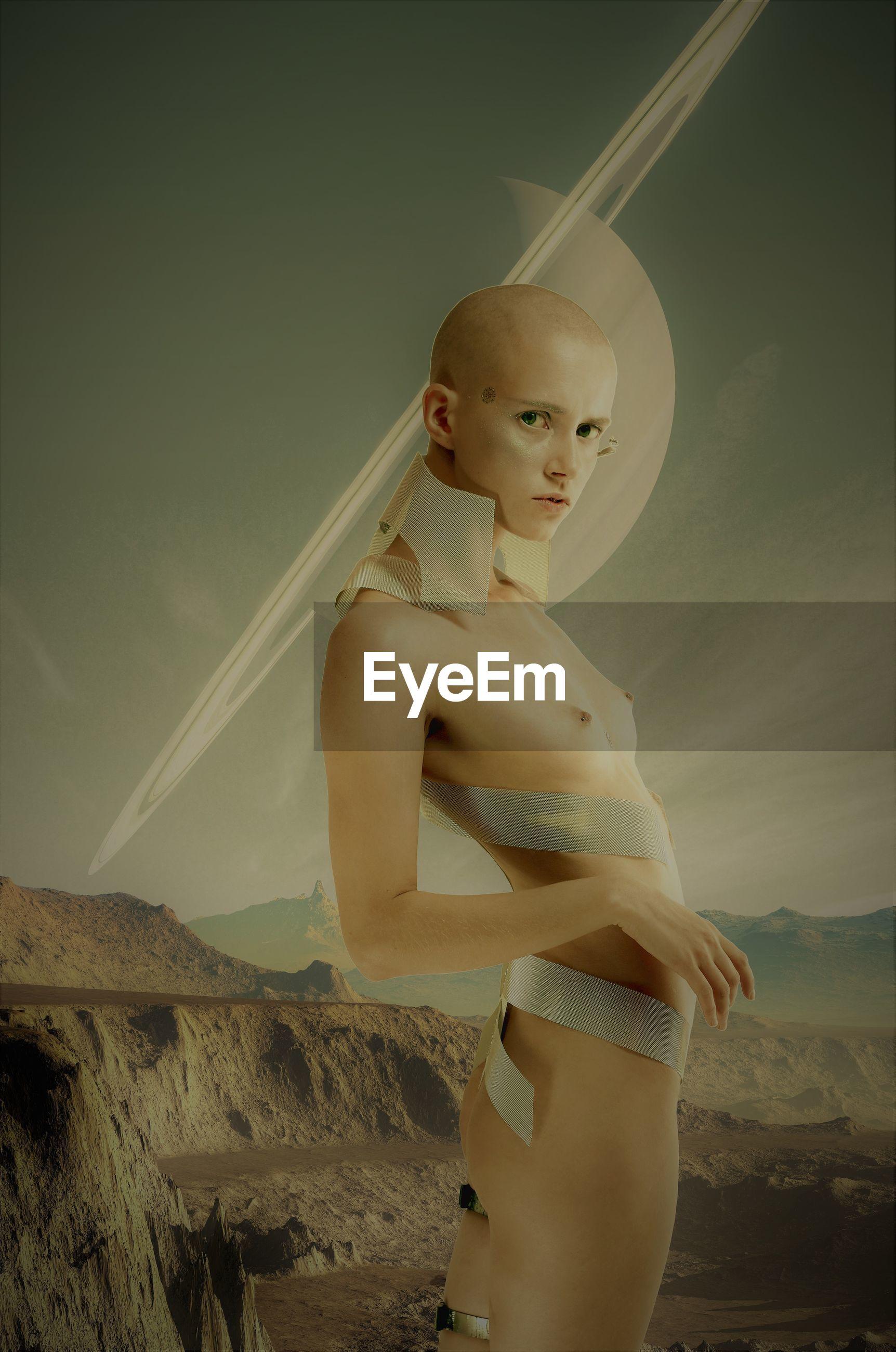 Portrait of naked alien standing against sky
