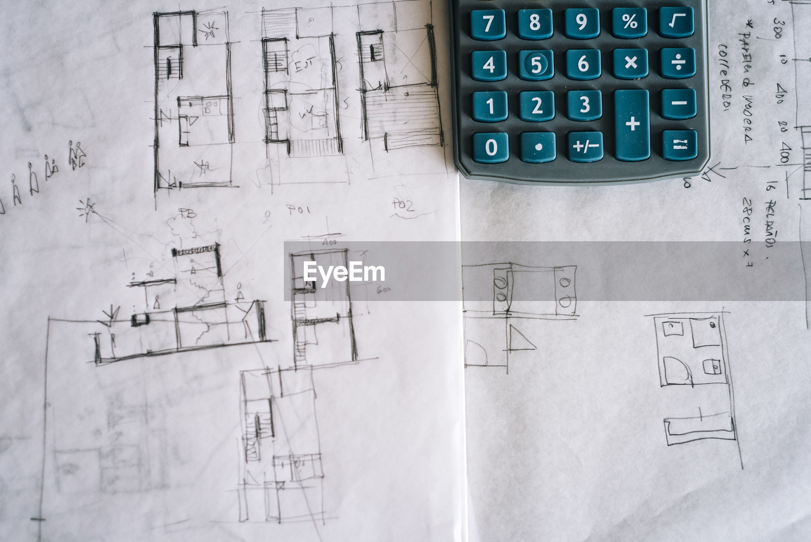 Close-up of blueprint with calculator