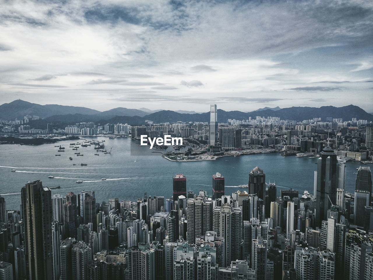 Aerial View Of Cityscape By River Against Cloudy Sky