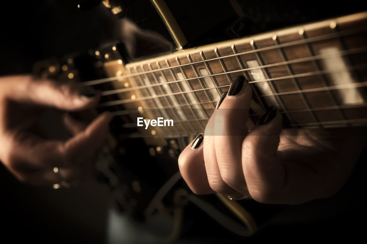 Close-Up Of Hands Holding Guitar
