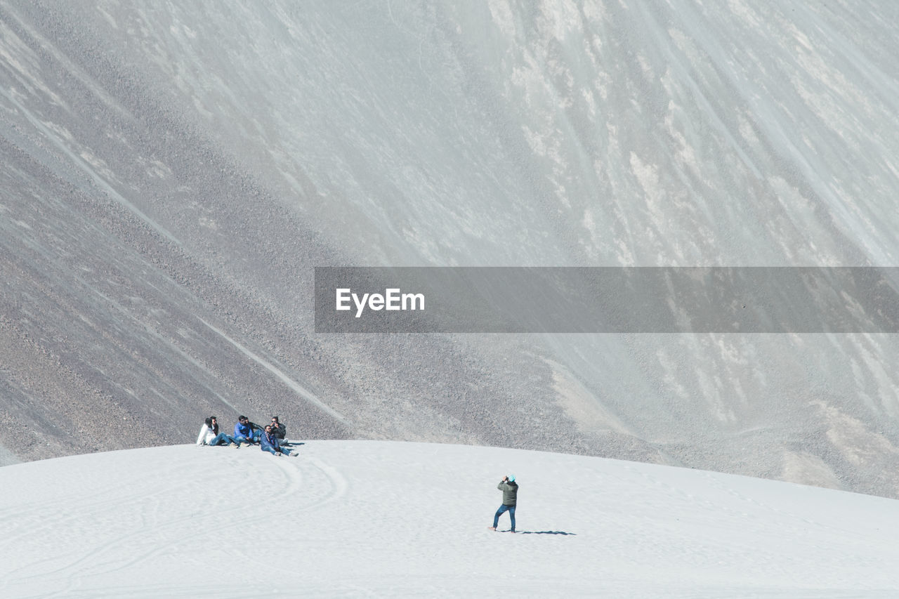 Friends Sitting On Snowcapped Mountain