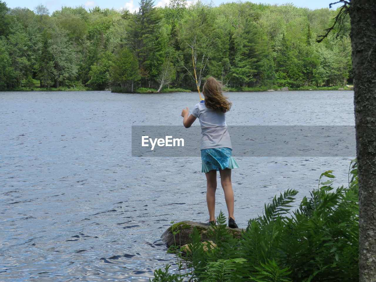 Rear view of girl fishing by lake against trees