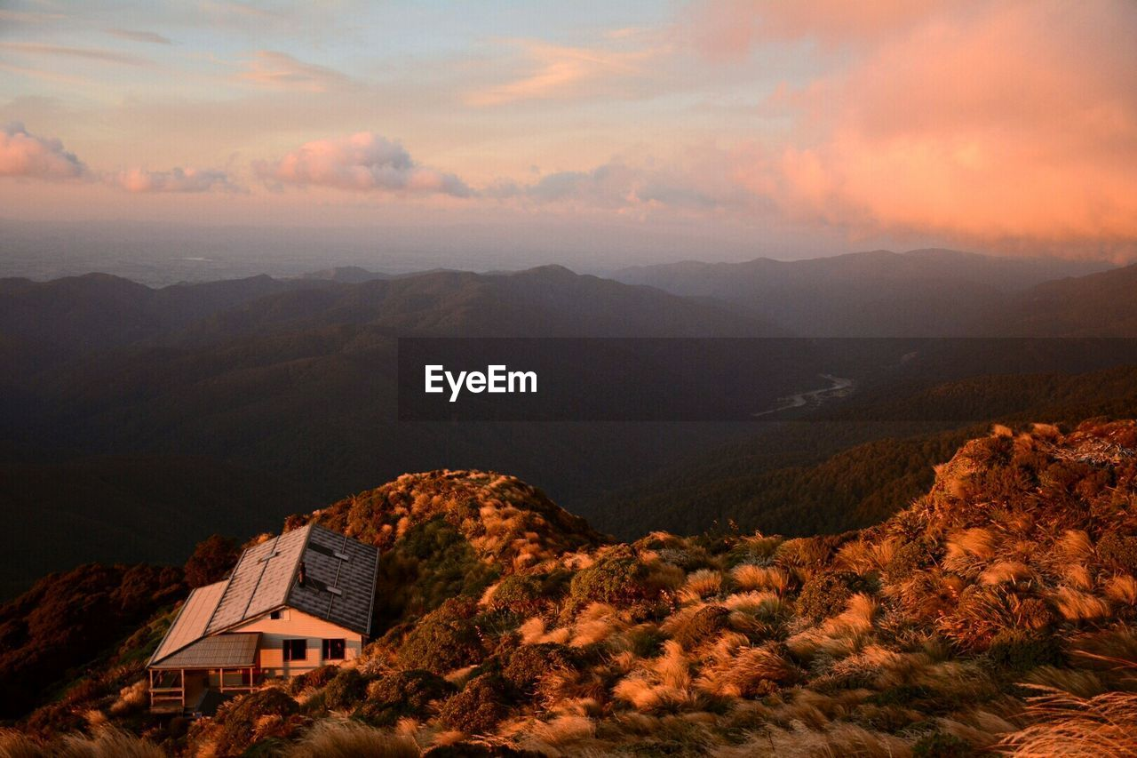 High Angle View Of House On Mountain Against Cloudy Sky