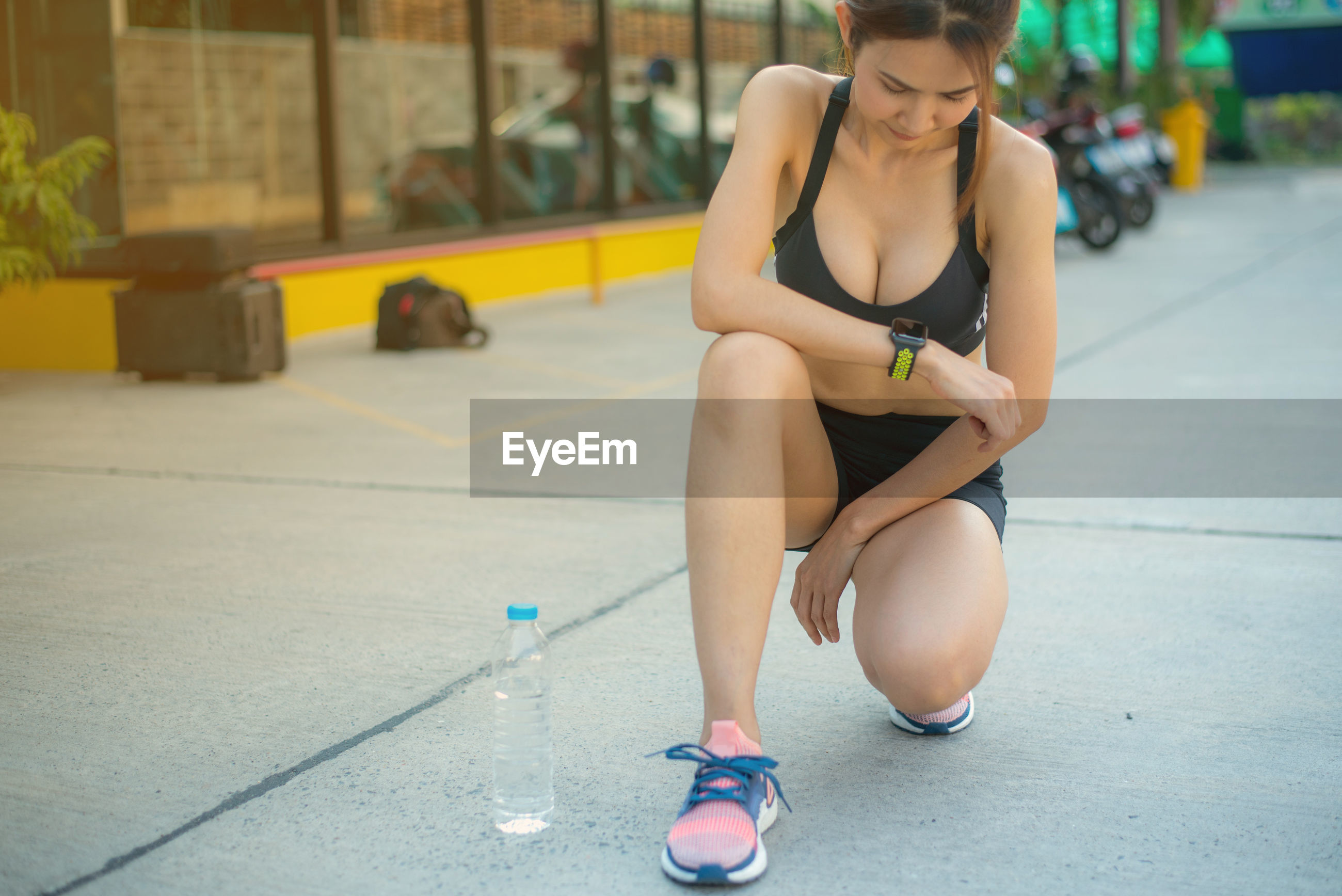 Full length of woman crouching on footpath