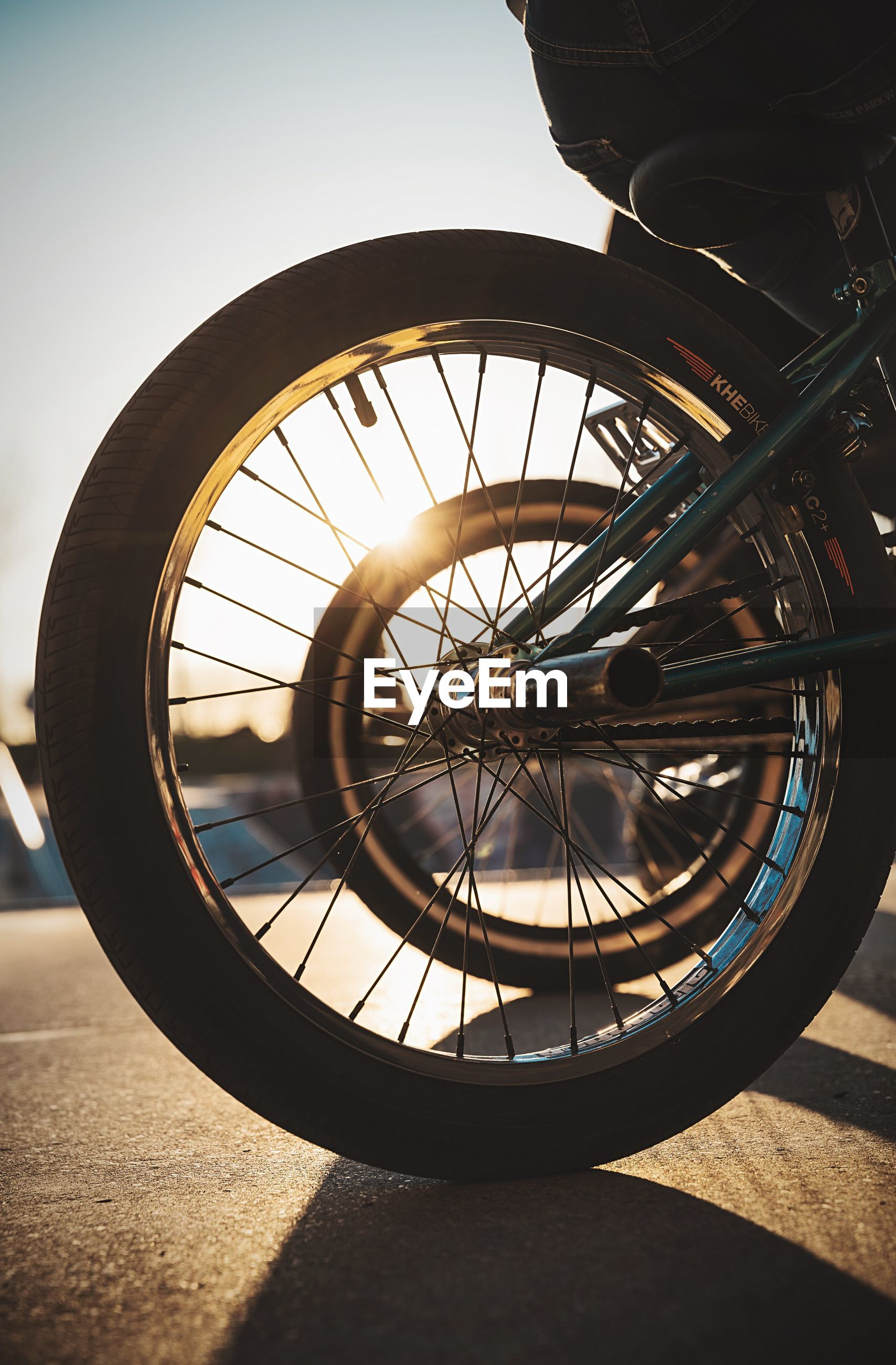 CLOSE-UP OF BICYCLE WHEEL BY STREET