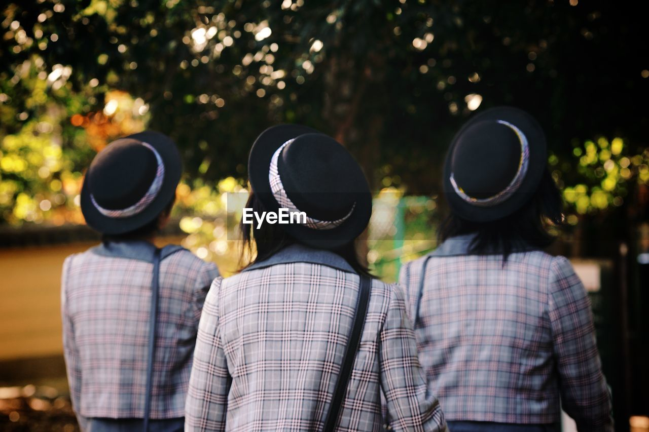 Rear View Of Female Students Walking Against Trees