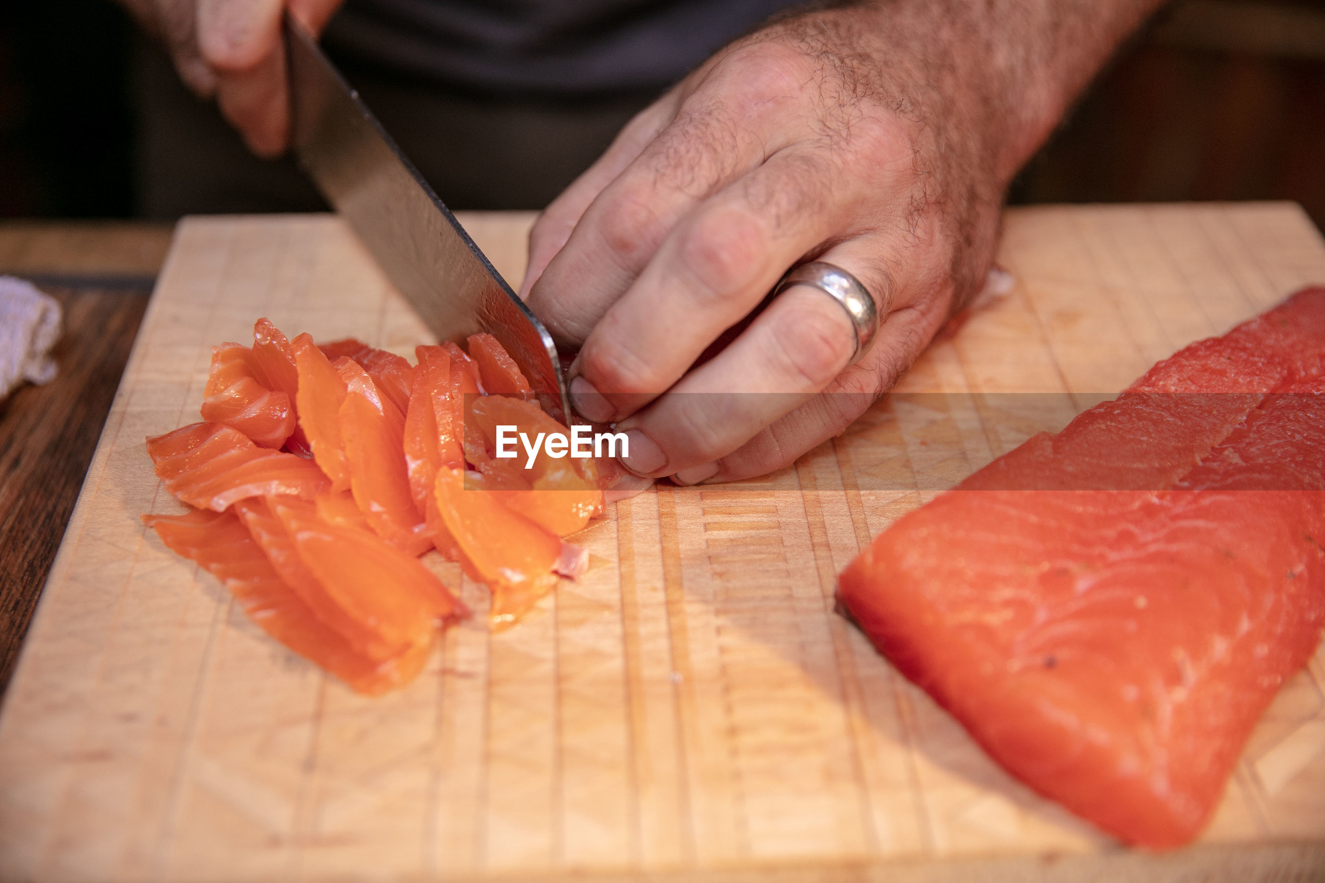 Cropped hands cutting salmon on cutting board