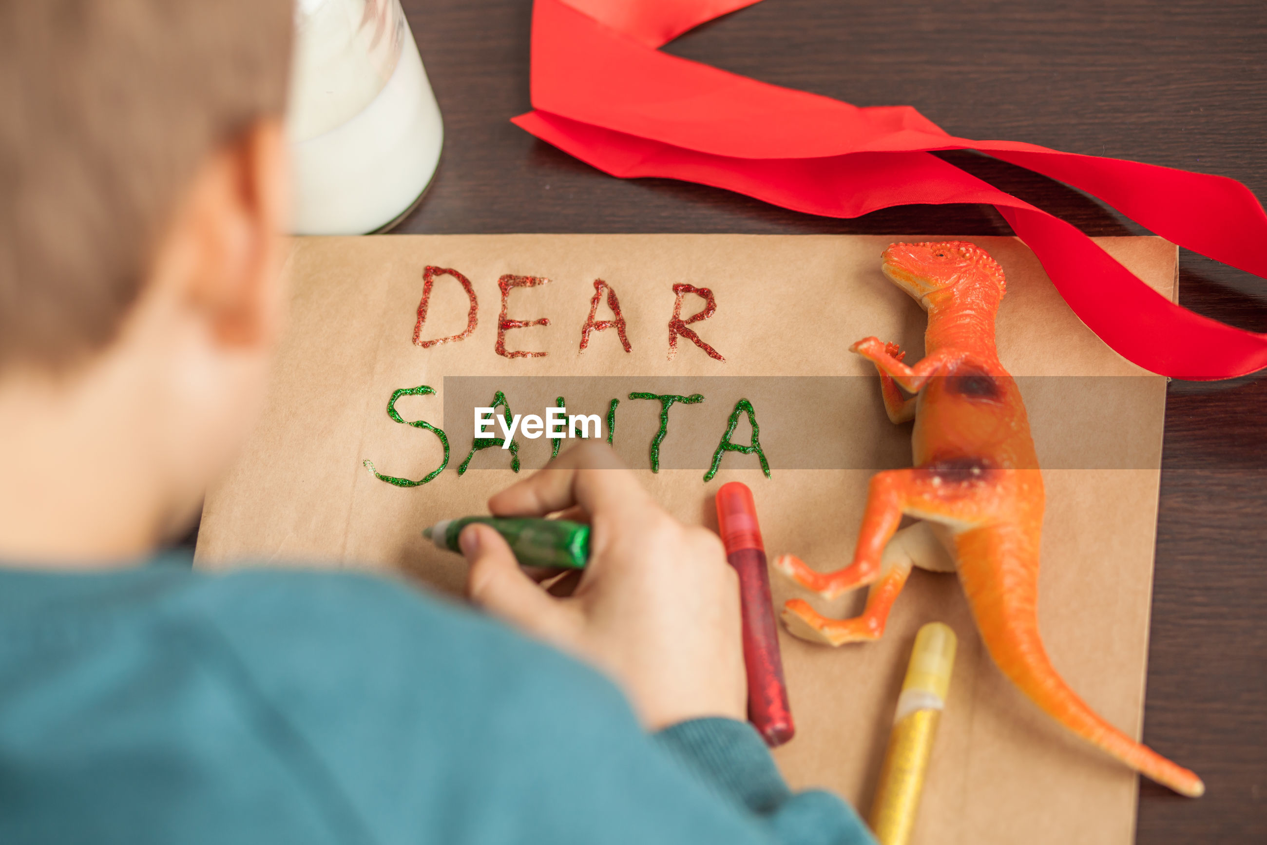 Rear view of boy making greeting card on table during christmas
