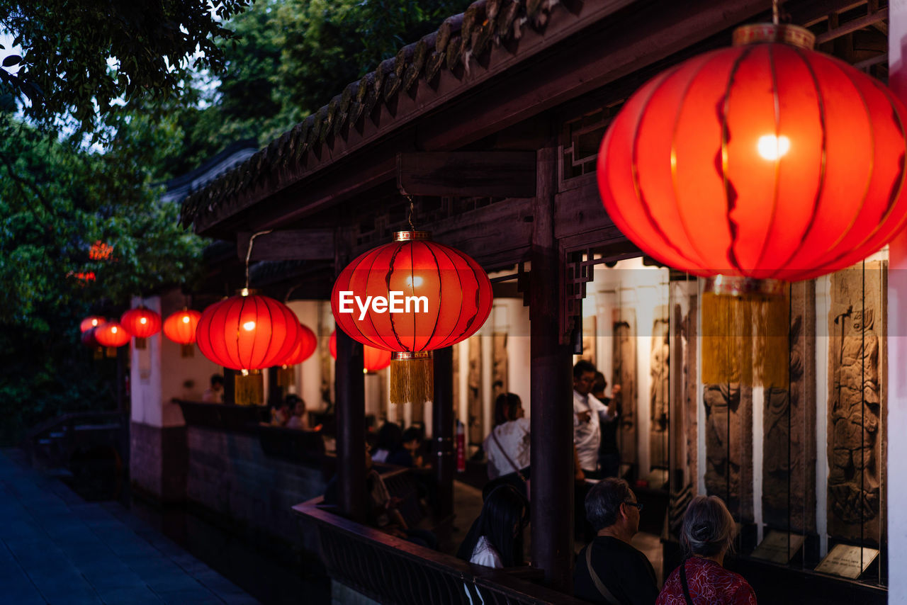 lighting equipment, lantern, chinese lantern, illuminated, red, decoration, hanging, built structure, architecture, incidental people, building exterior, communication, women, celebration, real people, night, in a row, outdoors, paper lantern, light, chinese lantern festival