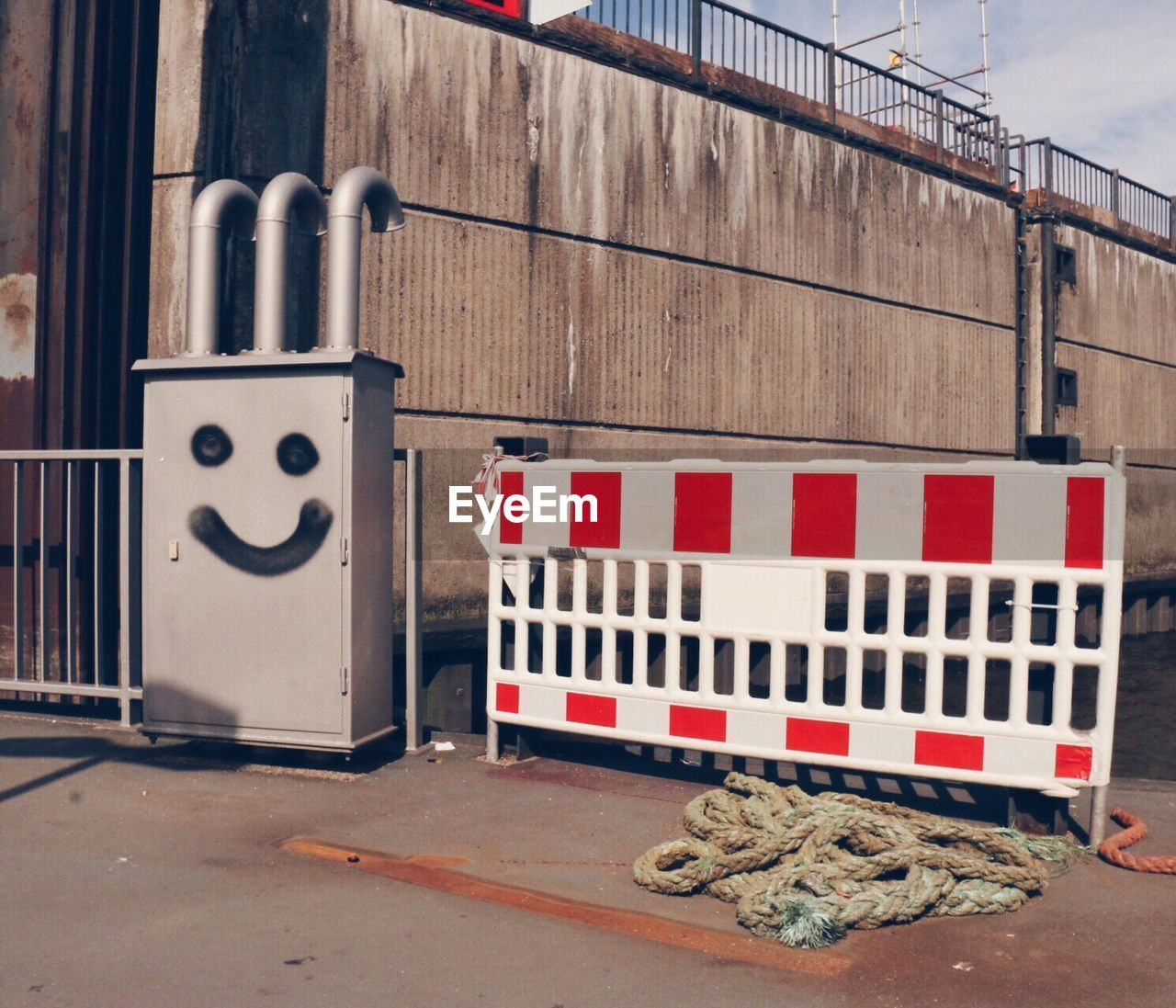 Anthropomorphic smiley face on metallic container by barricade on street