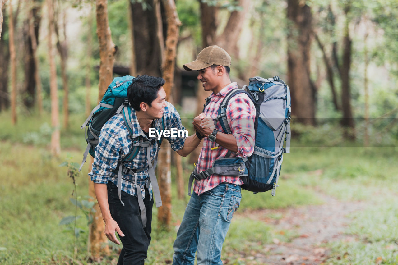 tree, forest, hiking, togetherness, leisure activity, backpack, land, young adult, men, plant, two people, adventure, young men, activity, travel, nature, casual clothing, young women, day, adult, outdoors, couple - relationship