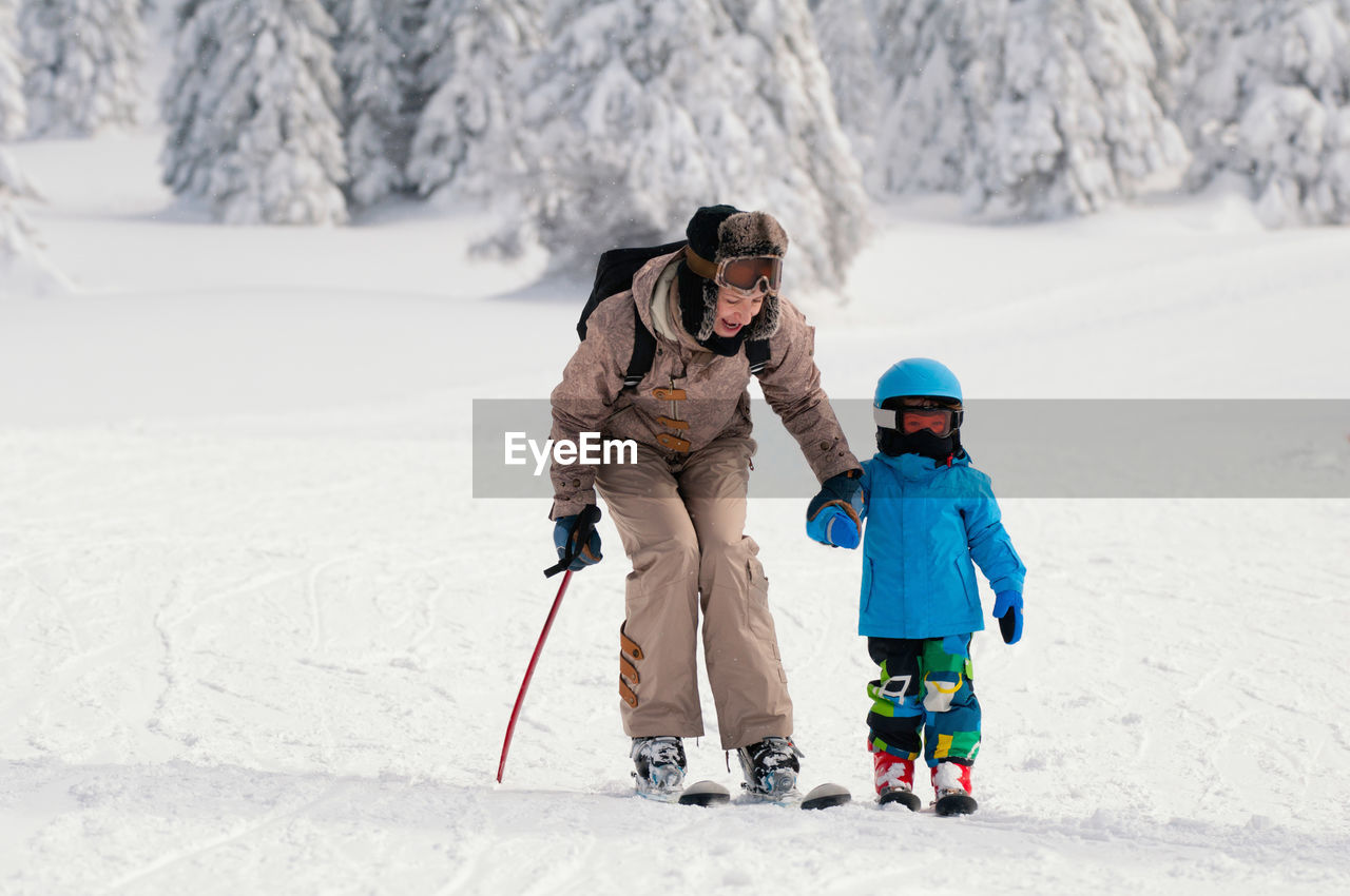 Mature Woman And His Son Skiing On Snow Covered Field