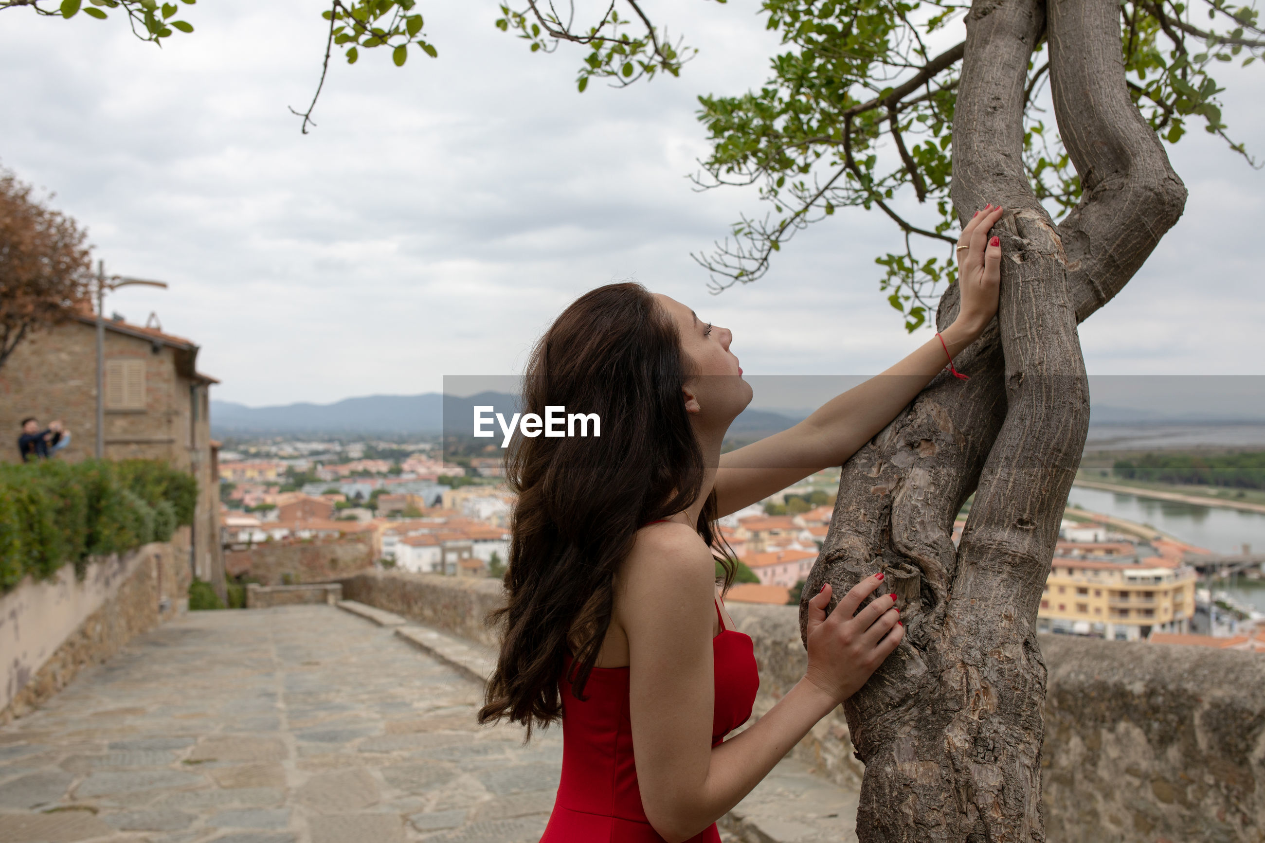 Side view of woman with long hair standing by tree