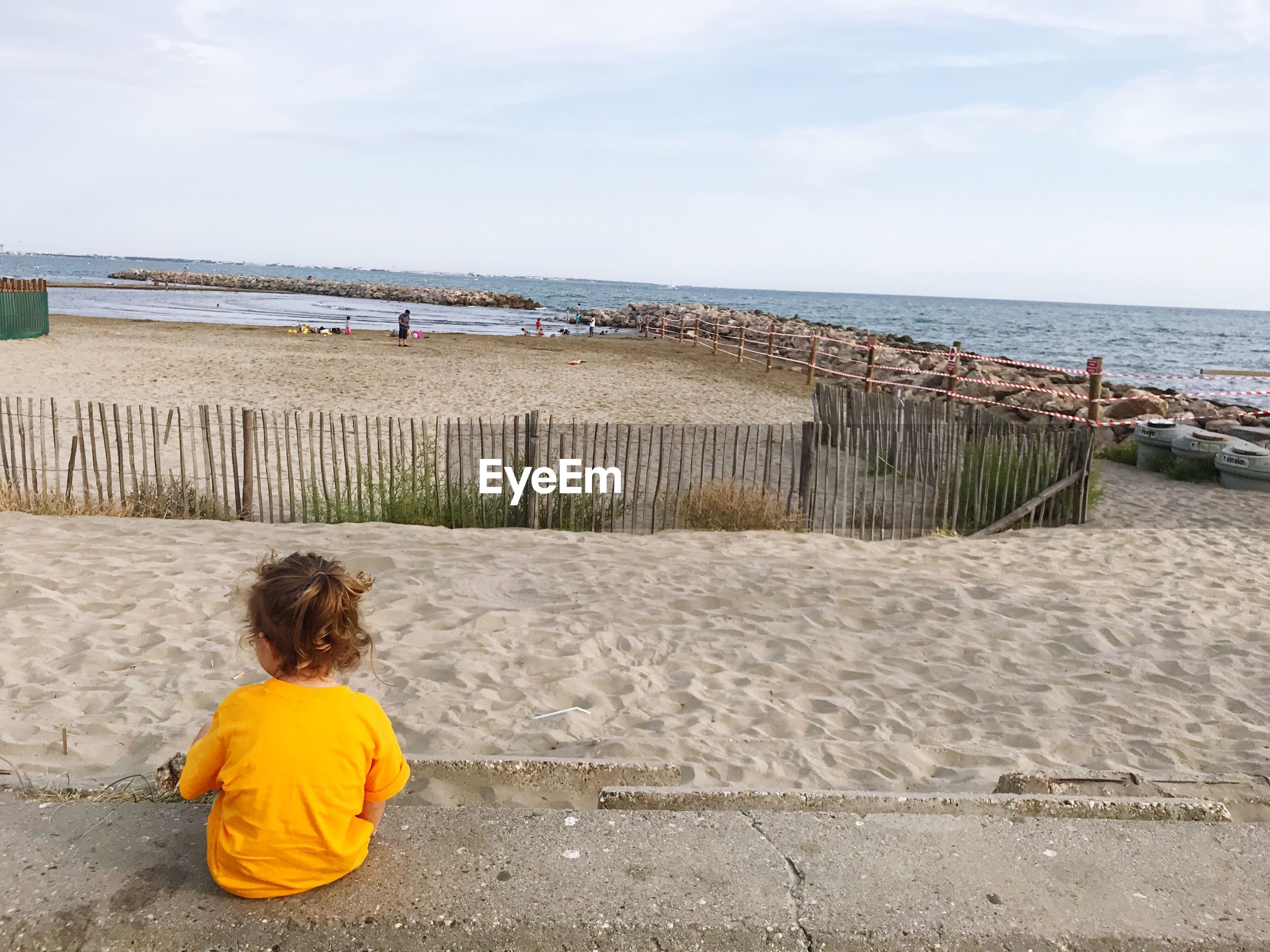 Rear view of girl sitting at beach against sky