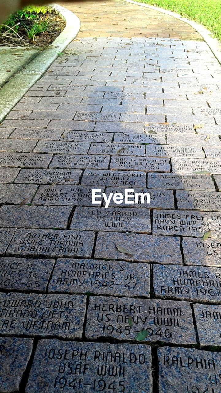 High Angle View Of Text Carved On Paving Stone Footpath In Park