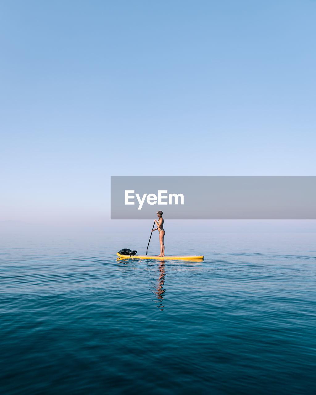 Woman paddle boarding on foggy lake on horizon