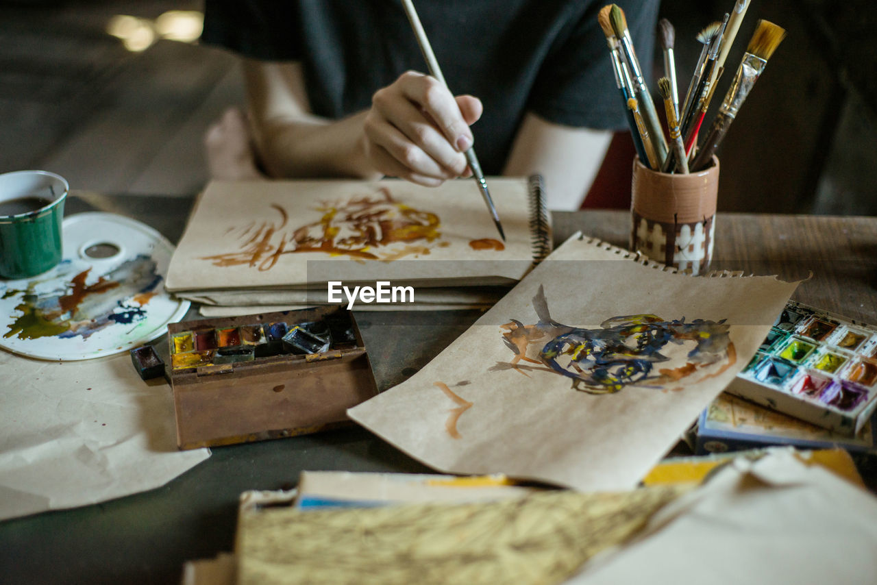 table, creativity, art and craft, indoors, craft, one person, brush, selective focus, occupation, artist, paintbrush, human hand, real people, paint, skill, drawing - activity, hand, human body part, palette, art and craft equipment, design professional