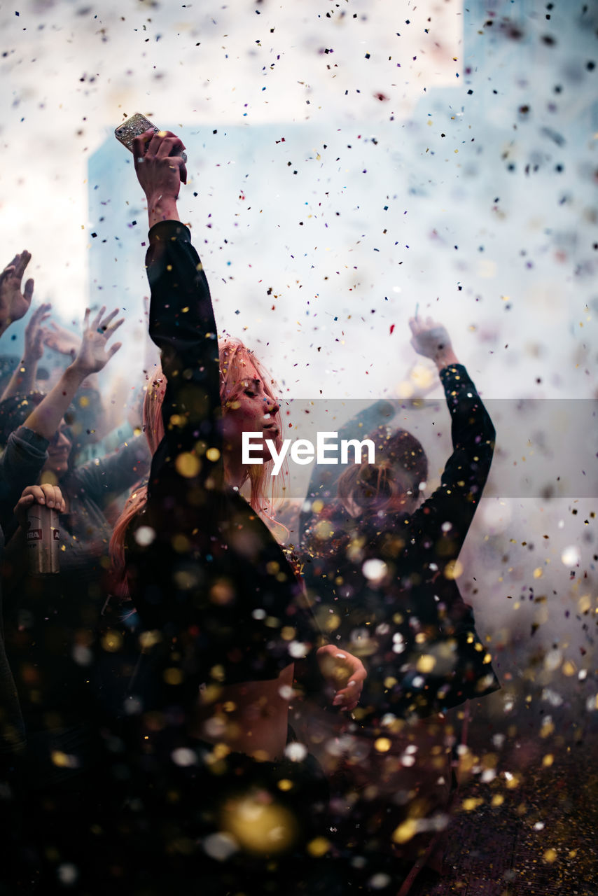 real people, men, celebration, happiness, group of people, event, adult, lifestyles, enjoyment, arms raised, people, togetherness, human arm, confetti, women, crowd, leisure activity, fun, party - social event, selective focus, hand, outdoors, hand raised