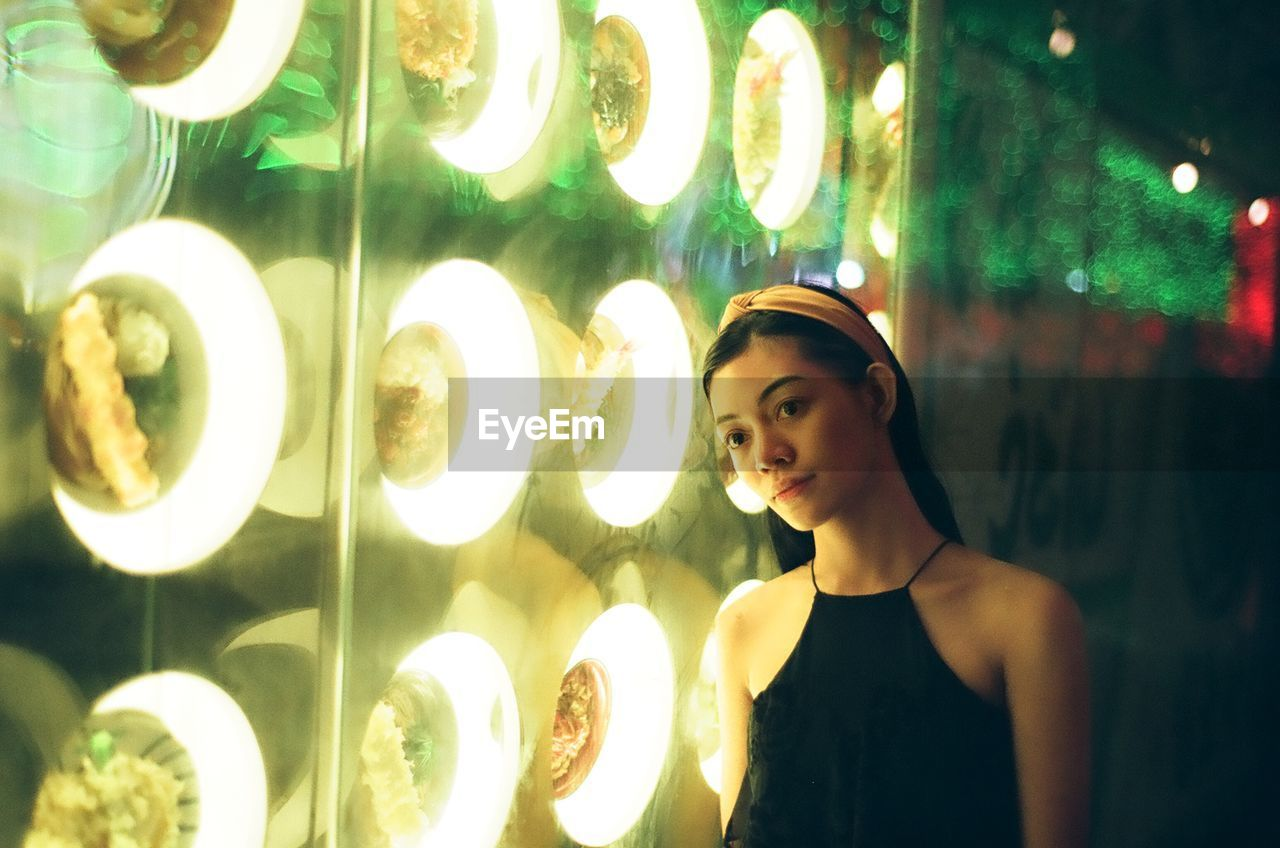 Young Woman Looking Away While Standing By Illuminated Window