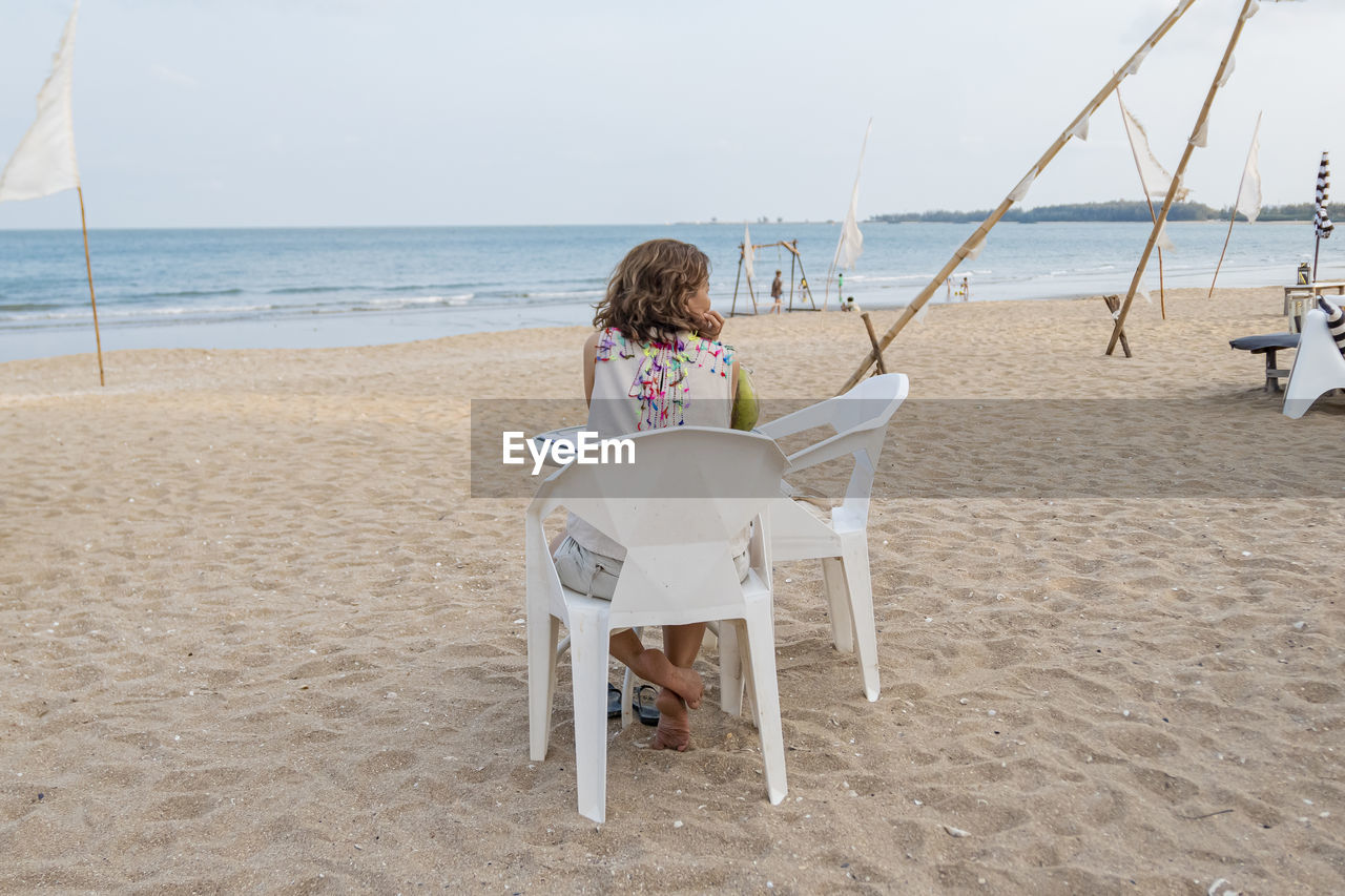 Rear view of woman sitting on chair at beach