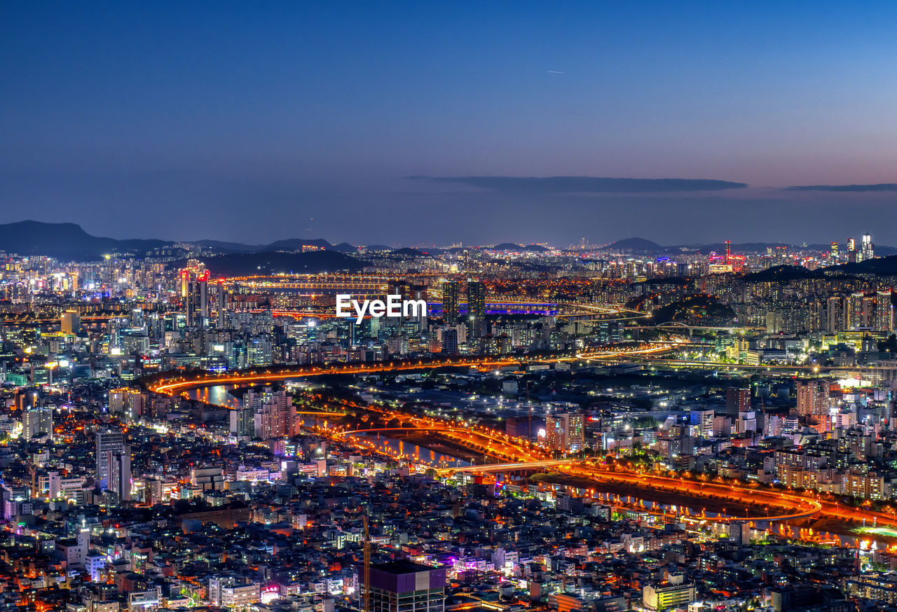 Aerial view of city at night against sky