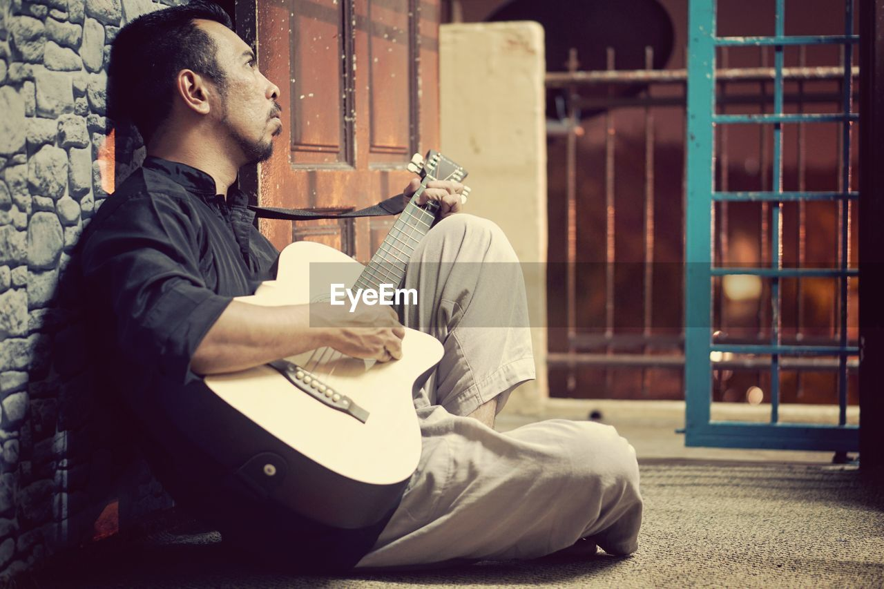 Man playing guitar while sitting by wall