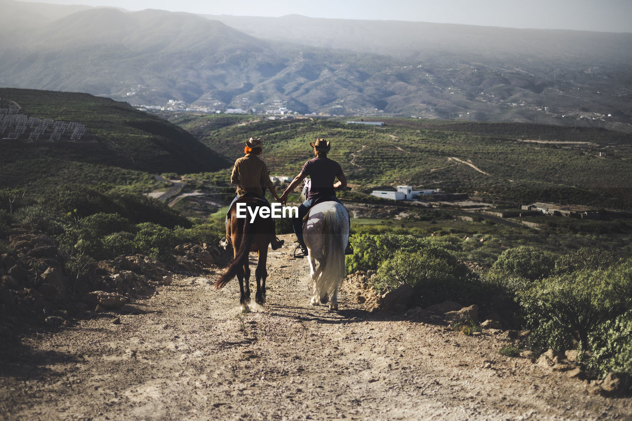People Riding Horses On Mountain Road Against Sky