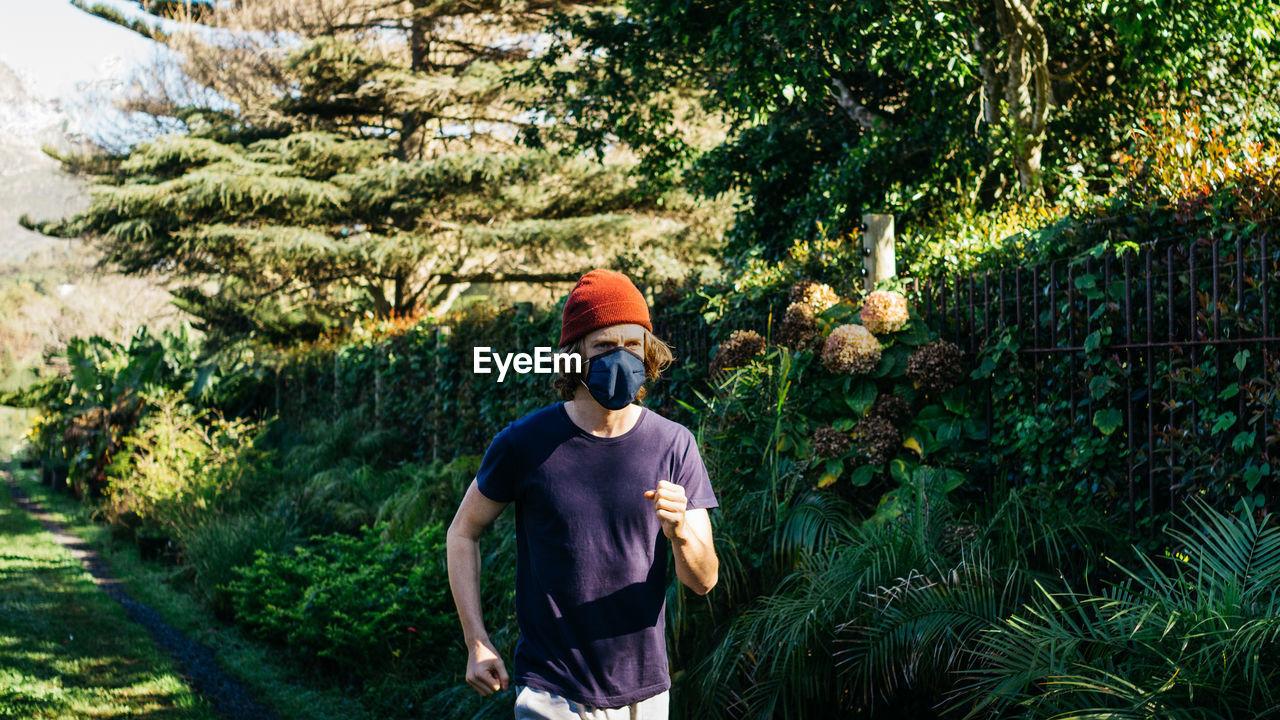 Man jogging against trees