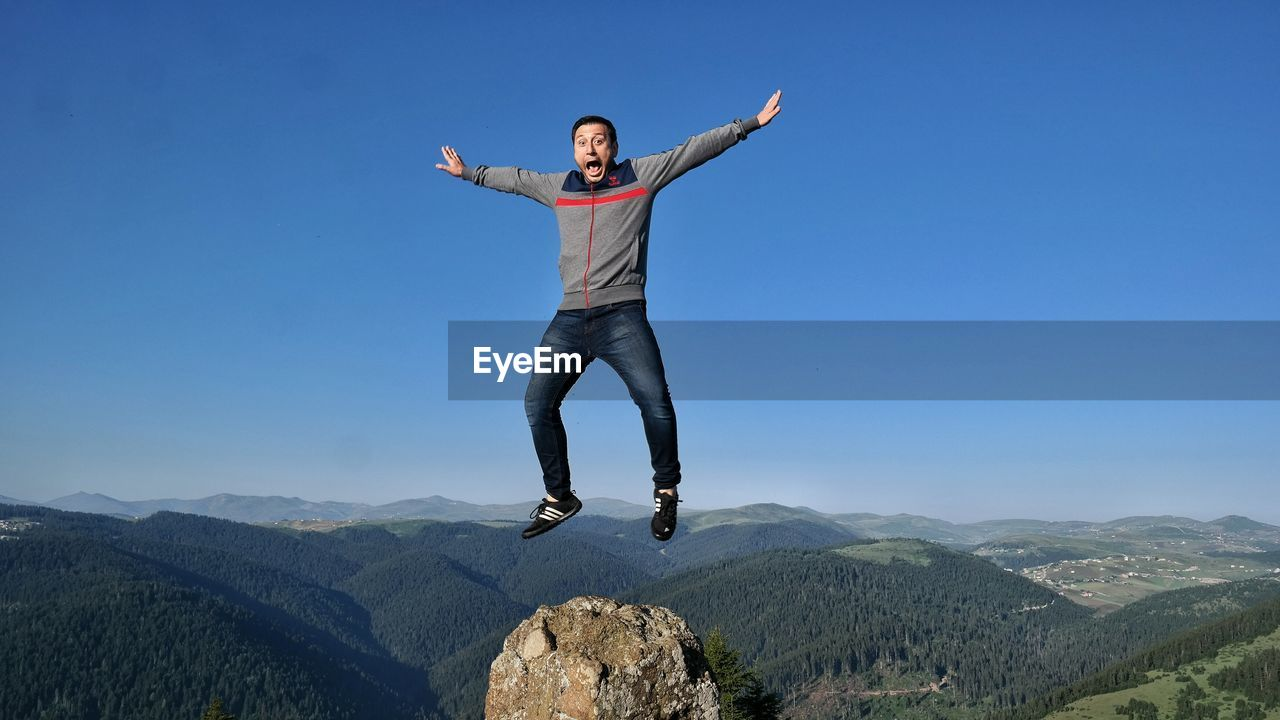 full length, real people, one person, young adult, mid-air, leisure activity, arms raised, jumping, day, outdoors, front view, casual clothing, lifestyles, young women, nature, clear sky, mountain, happiness, blue, energetic, sky, beauty in nature, people