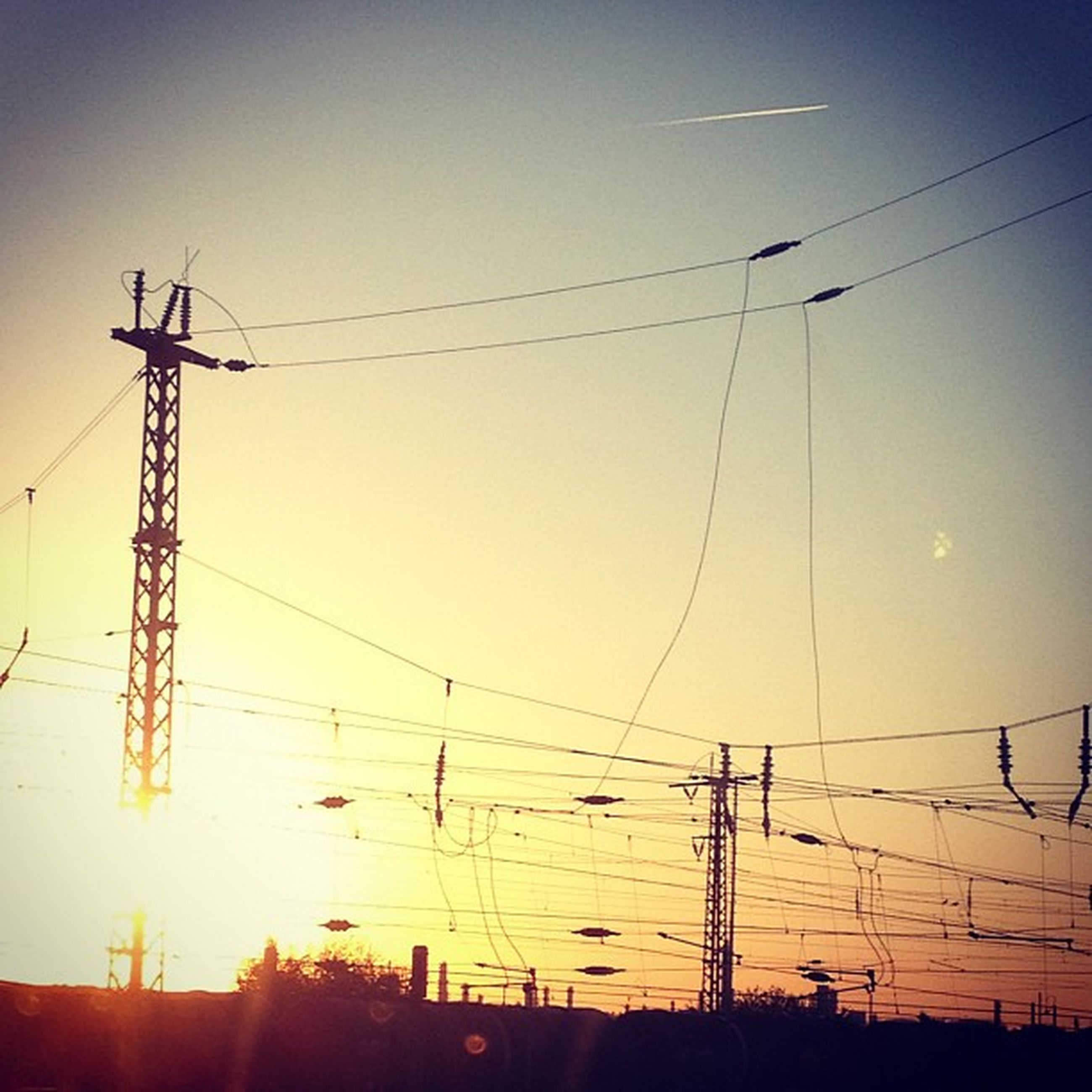 power line, electricity pylon, power supply, electricity, fuel and power generation, cable, connection, technology, sunset, low angle view, silhouette, power cable, clear sky, sky, complexity, sun, electricity tower, outdoors, no people, sunlight